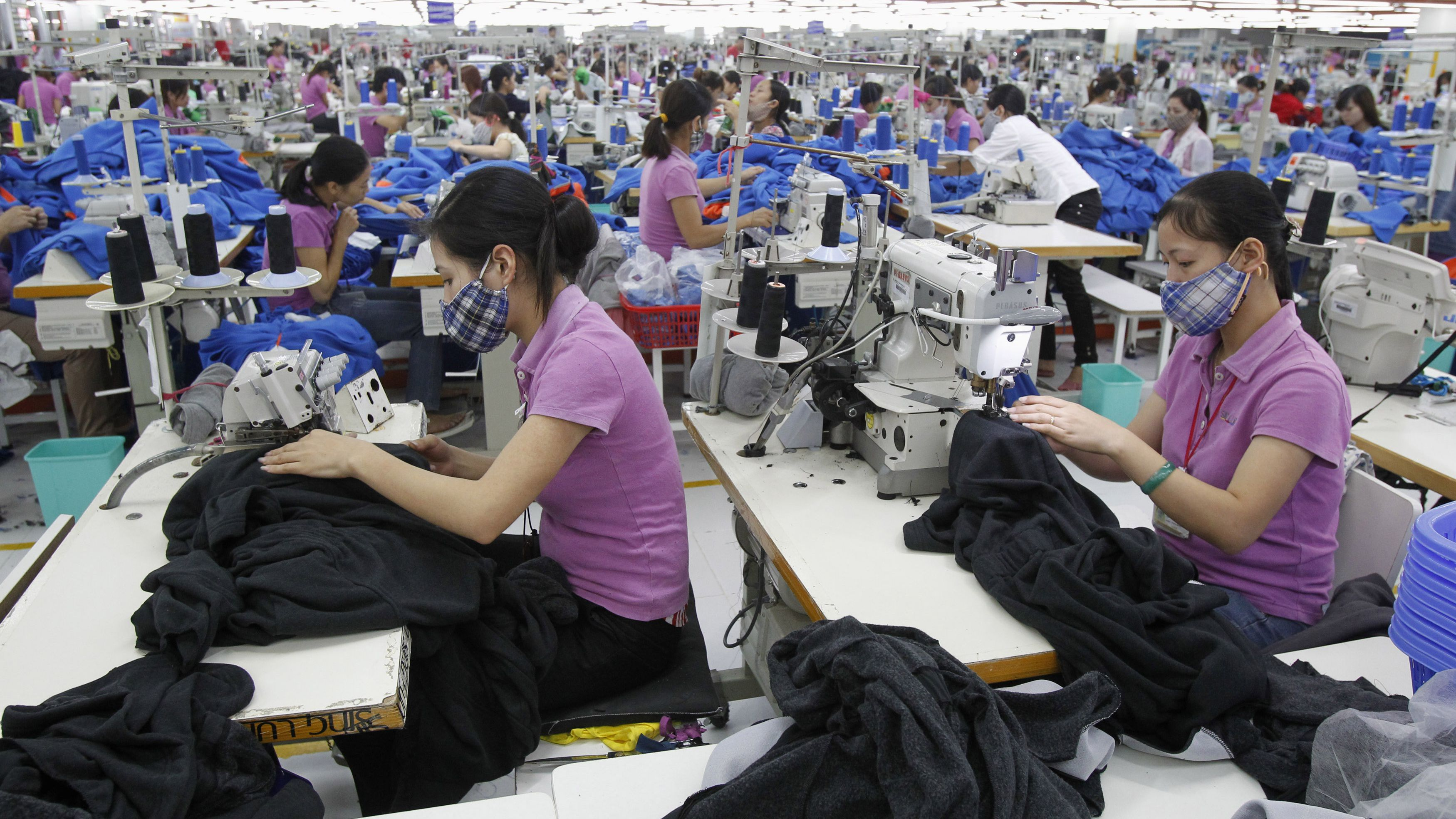 Labourers work at a garment factory owned by Singaporeans outside Hanoi October 19, 2012.