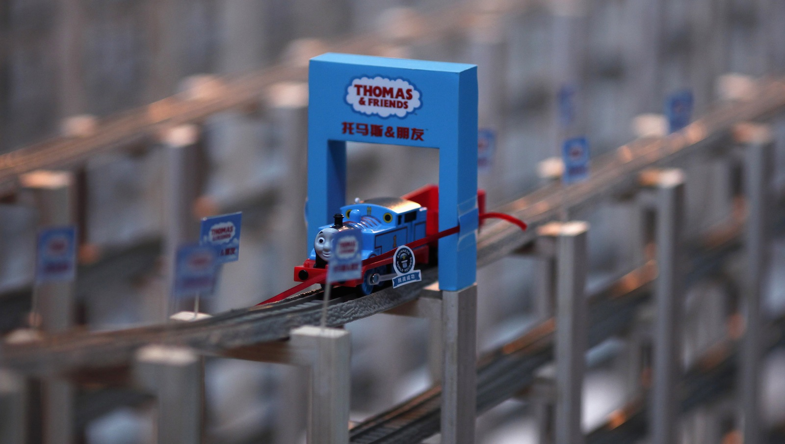 A staff member watches as a toy train travels along the 2.888-kilometer plastic track during an event organized by toy manufacturer Mattel to set a Guinness World Record in Shanghai November 24, 2012. Thomas & Friends, a brand belonging to the world's largest toy manufacturer Mattel, set the new record for the World's Longest Plastic Toy Train Track. The track was composed of 13,769 individual sections of plastic toy train track, forming a total of seven layers of track. The new world-record-winning track covers approximately 200 square meters, and the total length of the track measures six times the height of the Oriental Pearl TV Tower, 20% longer than the previous world record set in Odaiba, Japan.