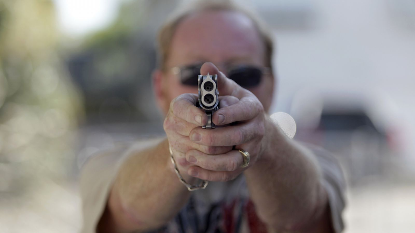 Doug Varrieur practices his firing stance on the firing range with an unloaded weapon in the yard of his home in Big Pine Keys in the Florida Keys March 5, 2014. Varrieur, 57, discovered a little-noticed part of Florida law which prohibits local governments from restricting gun rights in any way, and in December he set up a personal gun range on his property in a residential subdivision. Neighbors were outraged by the live gunfire, but their surprise was nothing compared to that of municipal leaders, who were shocked to realize there was nothing they could do about it. Picture taken March 5, 2014. REUTERS/Andrew Innerarity (UNITED STATES - Tags: SOCIETY) - RTR3G4NC