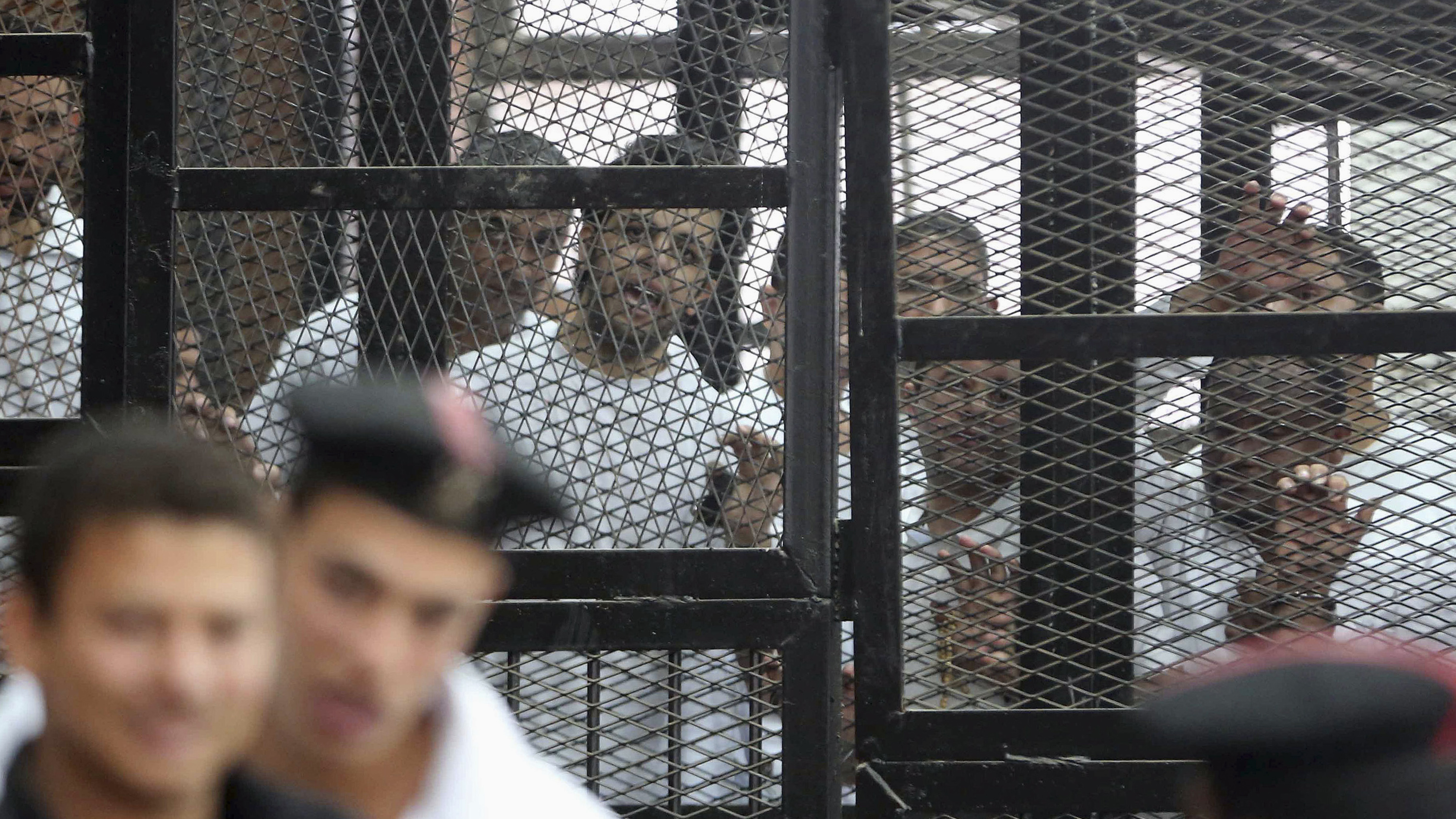 Al Jazeera's hunger striking journalist Abdullah Elshamy stands behind bars with other prisoners at a court in Cairo