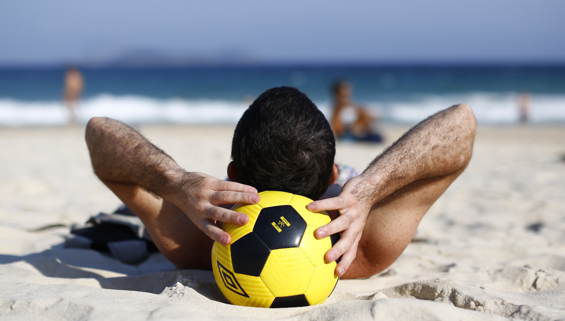 A man takes a nap over a soccer ball at Ipanema beach in Rio de Janeiro June 9, 2014. In a project called 'OnThe Sidelines' Reuters photographers share pictures showing their own quirky and creative view of the 2014 World Cup in Brazil.     REUTERS/Jorge Silva (BRAZIL)   - RTR3SY88