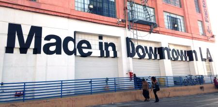Two people walk past the American apparel factory building and outlet store in Los Angeles, California July 7, 2014. Ousted American Apparel Inc head Dov Charney supported workers in the clothing industry with his stance in favor of immigration rights and determination to keep jobs in the United States, but some employees are not returning the favor. Last month American Apparel's board dismissed Charney. It accused the chairman, president and chief executive of misusing corporate funds and failing to prevent the dissemination of nude photos of a female ex-employee who sued him. Picture taken July 7, 2014.