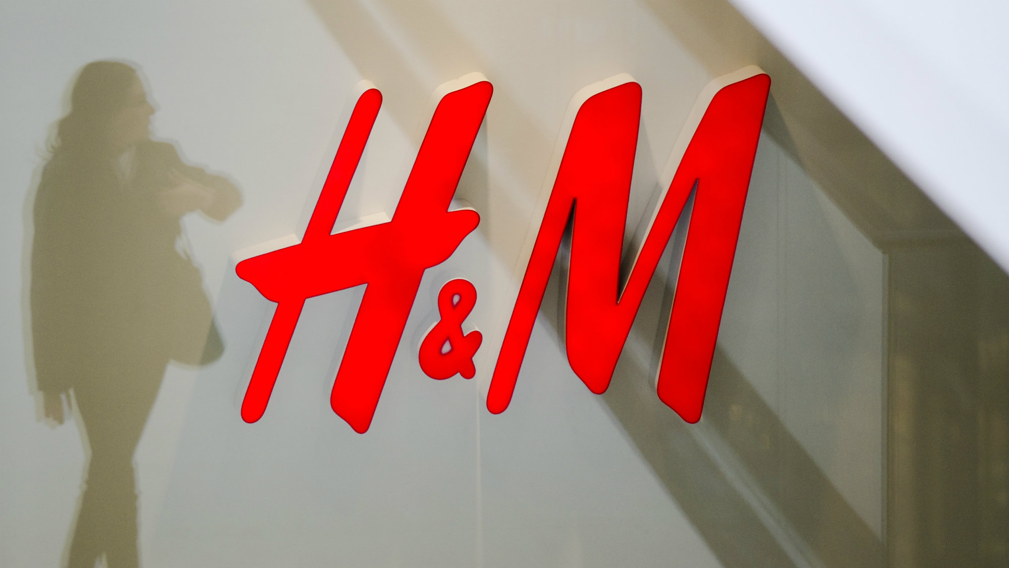 A woman is reflected next to the logo of the H&M fashion retailer in the newly opened Mall of Berlin shopping center.