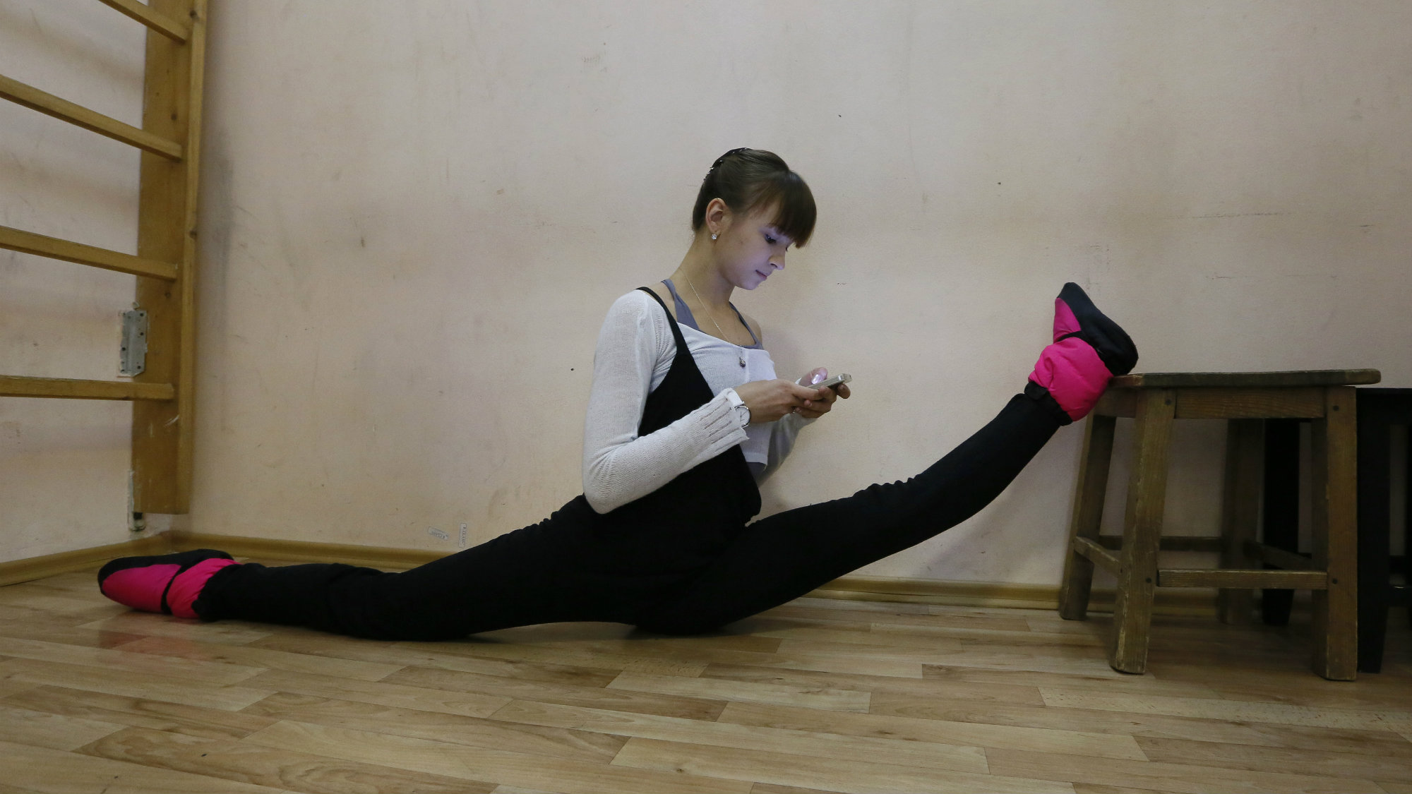 A ballet dancer uses her smartphone as she stretches backstage before her performance.