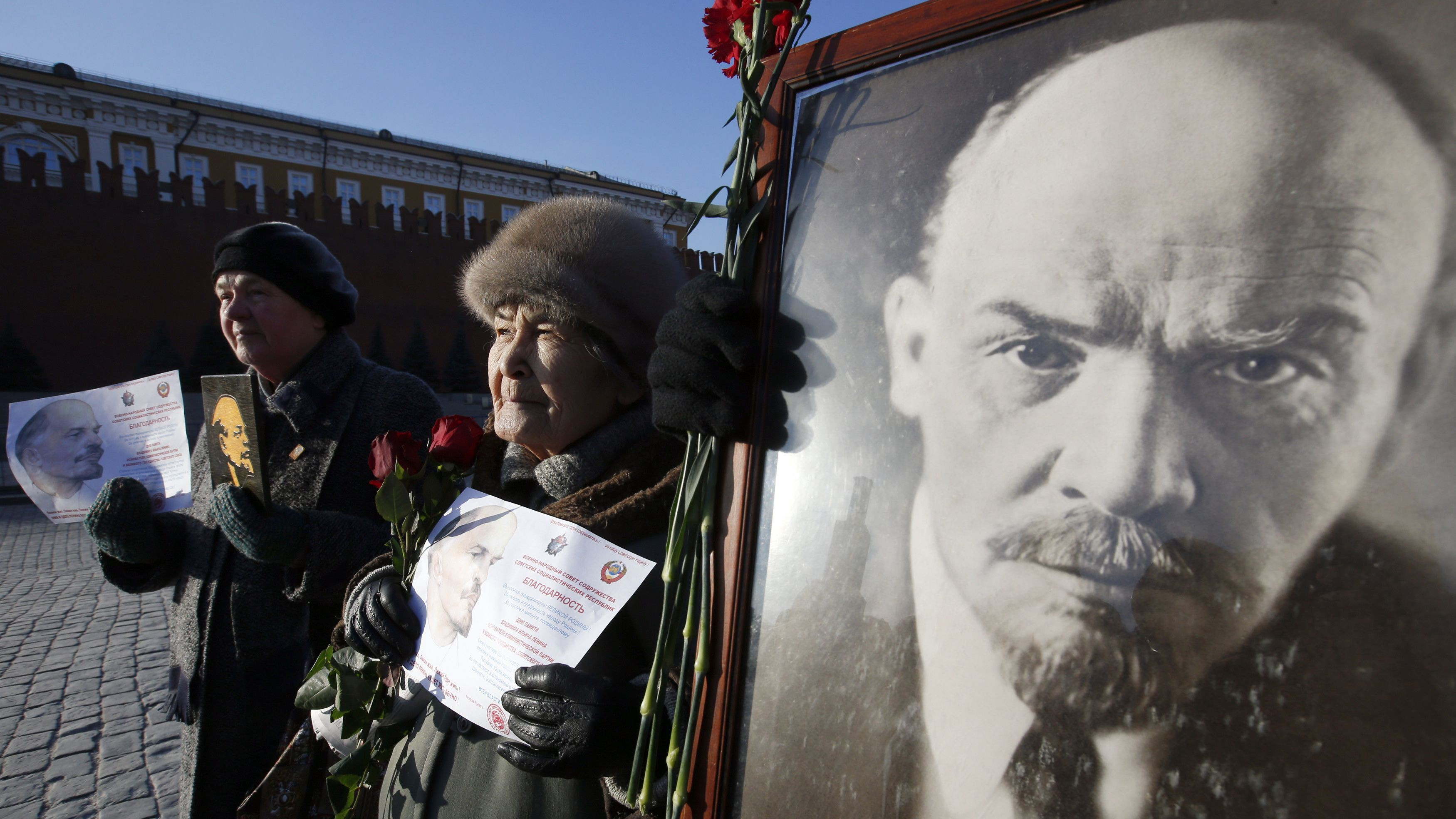 Communist supporters hold portraits of Soviet state founder Lenin during a wreath laying ceremony to Lenin's mausoleum on Moscow's Red Square
