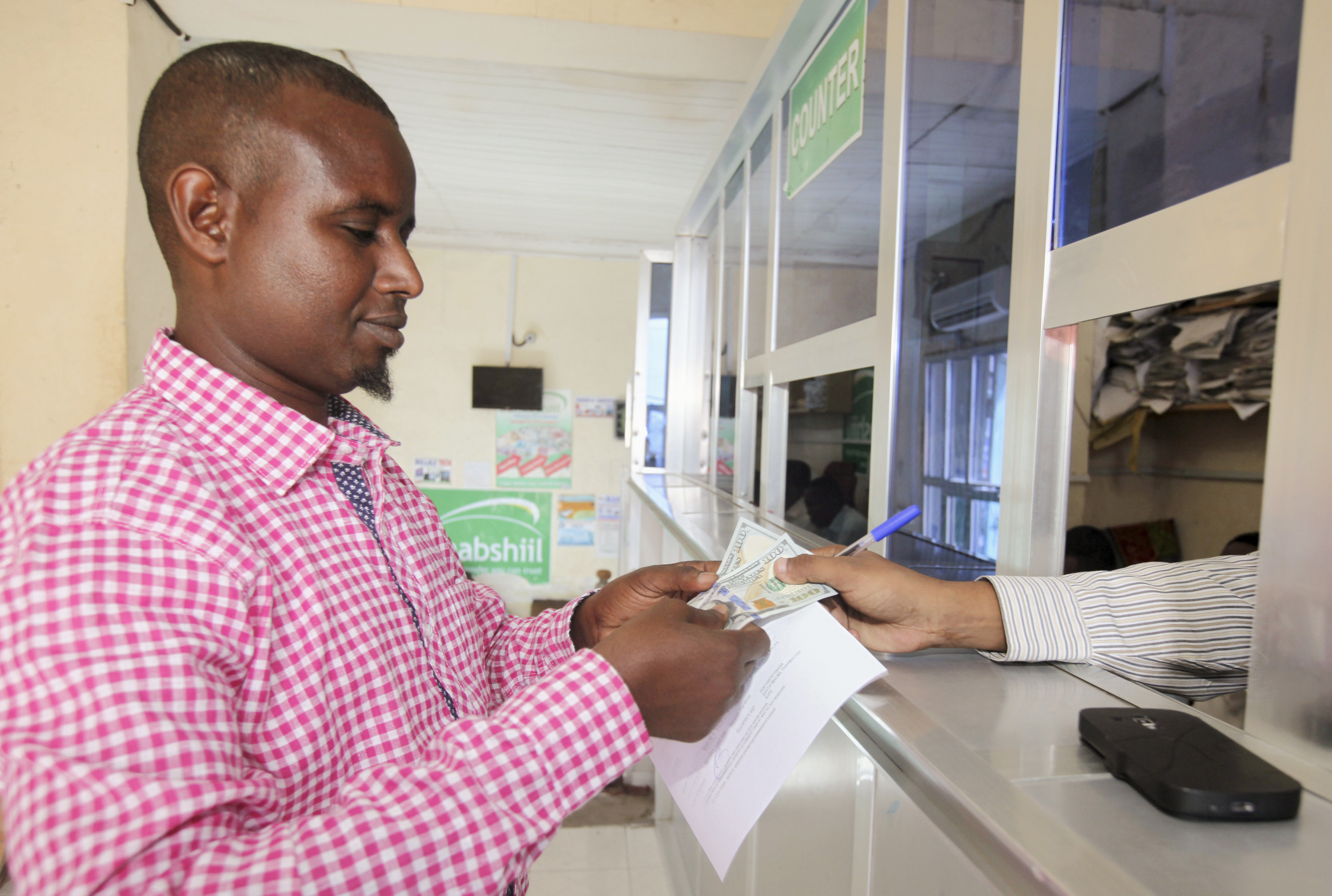 A customer receives U.S. notes from a teller at the Dahabshill money transfer office in capital Mogadishu February 16, 2015. Somalia's prime minister last week urged the U.S. government and U.S. banks to support money transfer firms that offer a lifeline for many in the war-torn Horn of Africa nation. About 40 percent of all Somali families rely on remittances from another country, and the estimated annual total of $1.3 billion is more than all foreign aid and investment in Somalia combined.