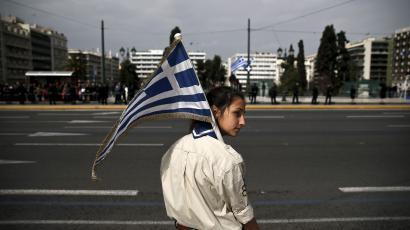 A girl scout holds a Greek national flag ahead of a student parade in Athens