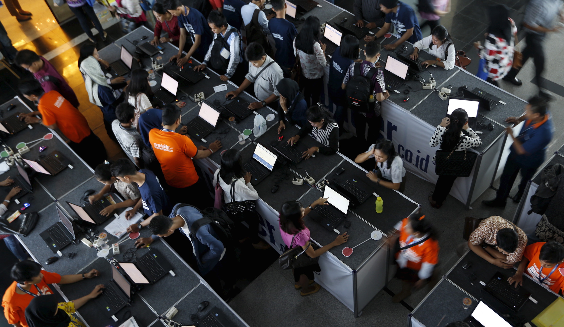 Indonesian youths fill up job application forms on laptops during the Career & Higher Education Fair in Jakarta, April 10, 2015.  After Indonesia was crushed in the Asian financial crisis - its economy shrank 13 percent in 1998 - the battered rupiah helped it start to export its way back to growth. Now, Southeast Asia's biggest economy is growing at its slowest pace in five years, 5 percent, and the currency recently tumbled to its weakest since 1998. The rupiah's 9.3 percent slide against the dollar since June should help Indonesian manufacturers who export clothes, shoes and other products cut prices and win orders. But it isn't working that way, due to Indonesia's rising wage costs and other factors. Problems with infrastructure and bureaucracy have added to pessimism that factories can lift exports and give Indonesia a boost it needs as the coal and commodity boom which fueled growth for years is history. REUTERS/Beawiharta - RTR4WR6J