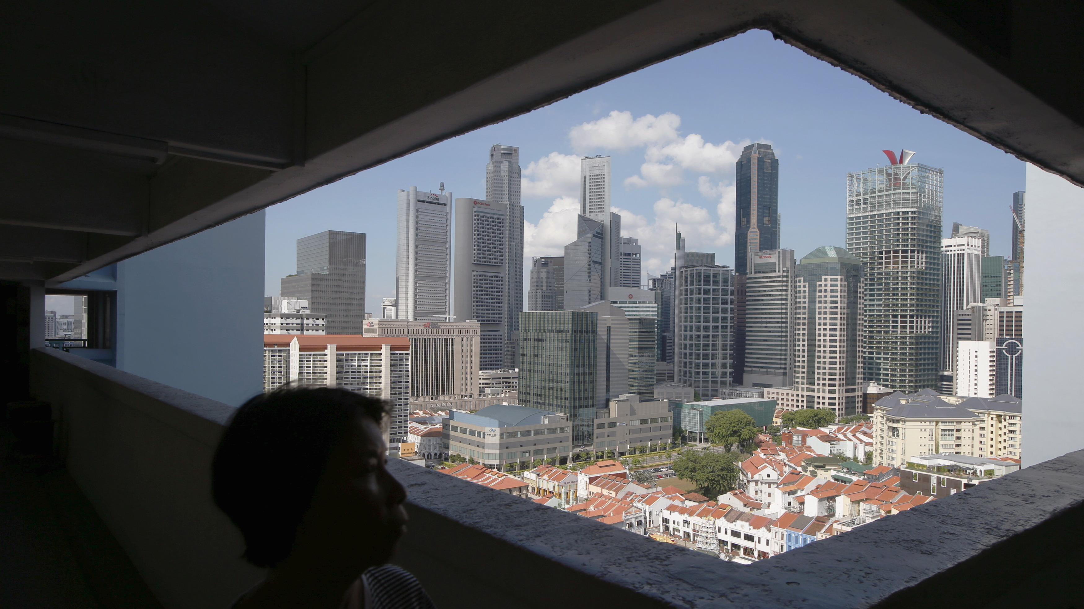 A woman passes the skyline of the central business district, in a public housing estate in Singapore