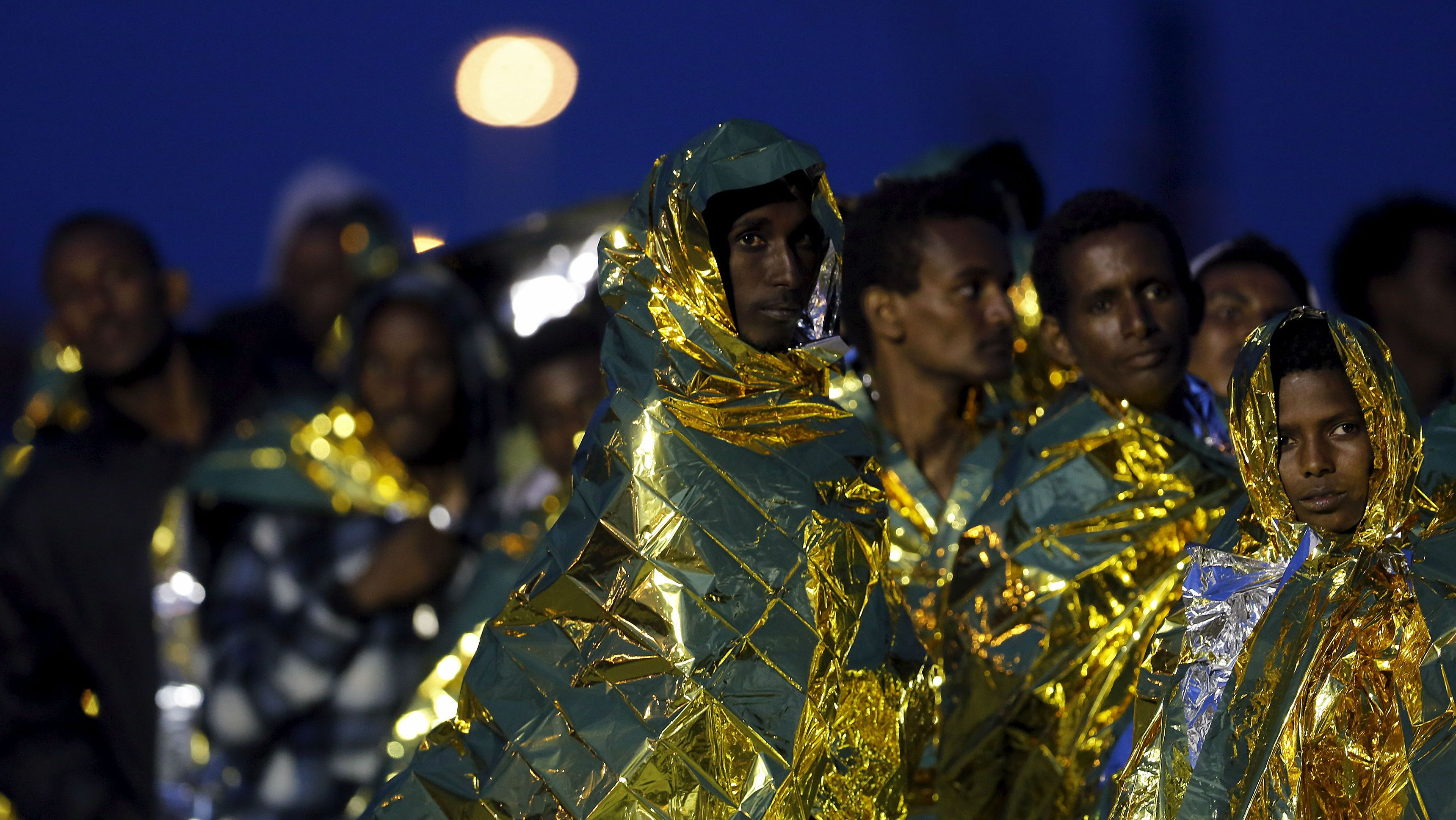 Migrants cover themselves with thermal blankets as they stand in line after disembarking in the Sicilian harbour of Augusta, Italy, May 30, 2015. Close to 1,000 migrants rescued in on-going operations are brought safely to port in Sicily as Italian authorities say over 4,000 migrants have been saved from the Mediterranean in twenty-four hours and 17 migrants have been found dead on a boat. REUTERS/Antonio Parrinello
