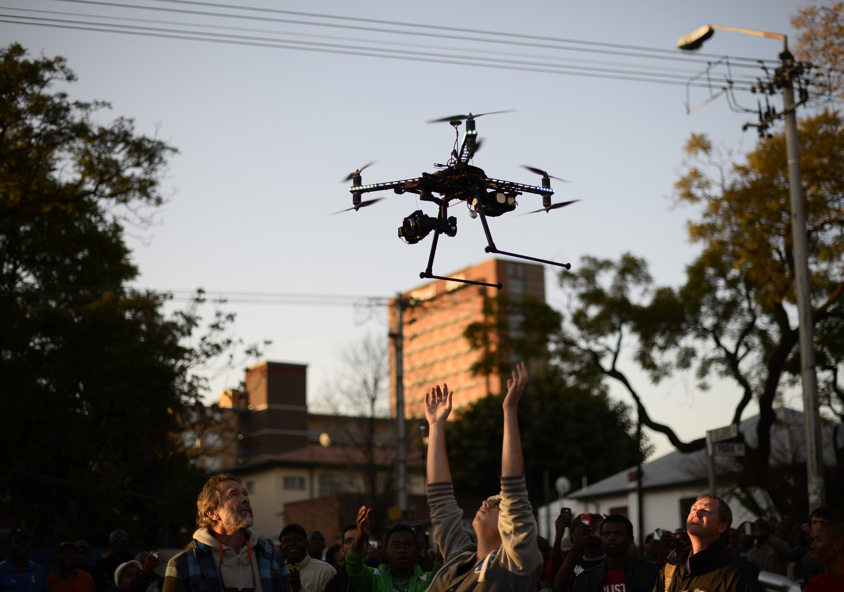 A man reaches out to catch a radio-controlled helicopter drone with a camera outside the clinic where Mandela is being treated in Pretoria