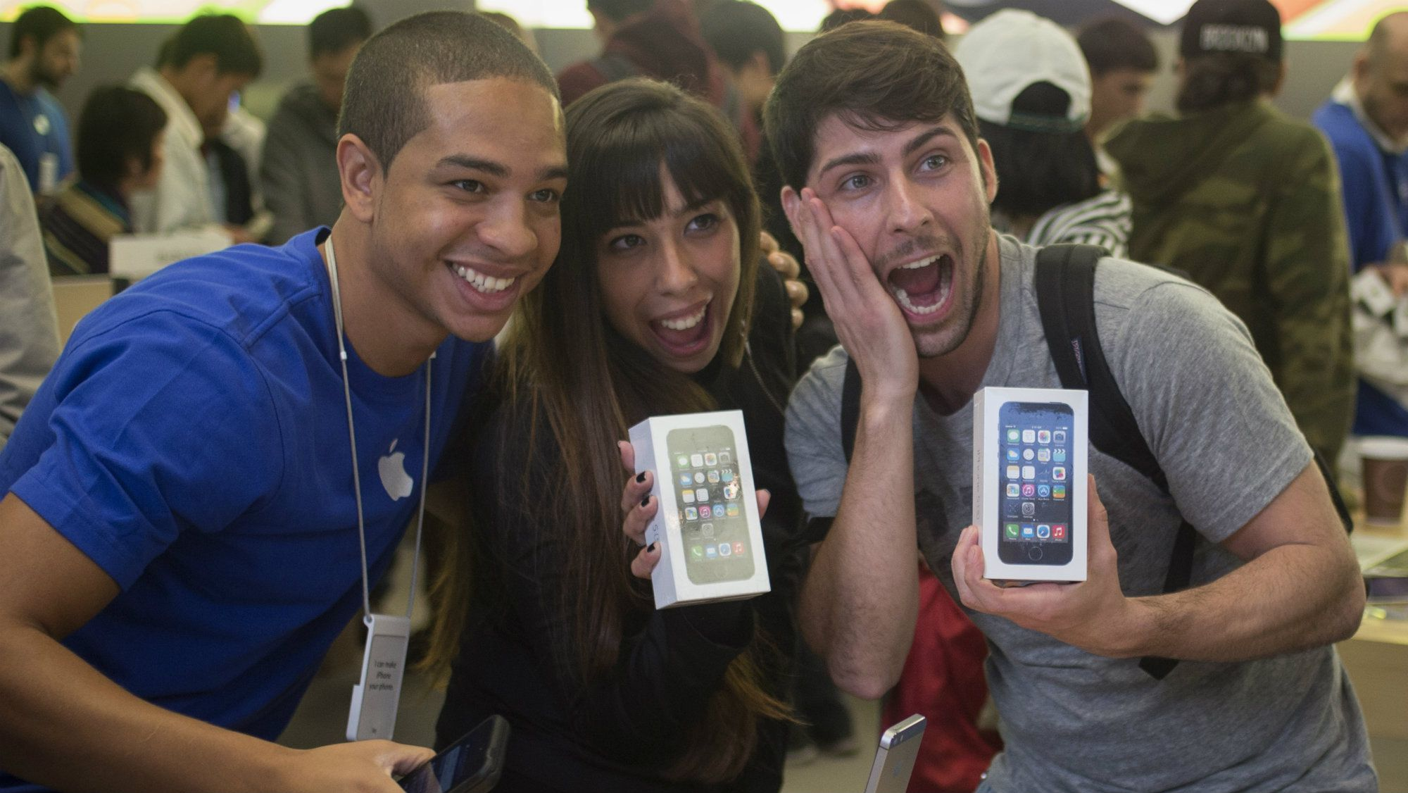 Customers pose with their new Apple iPhone 5s phones with an Apple employee at the Apple Retail Store on Fifth Avenue in Manhattan, New York.