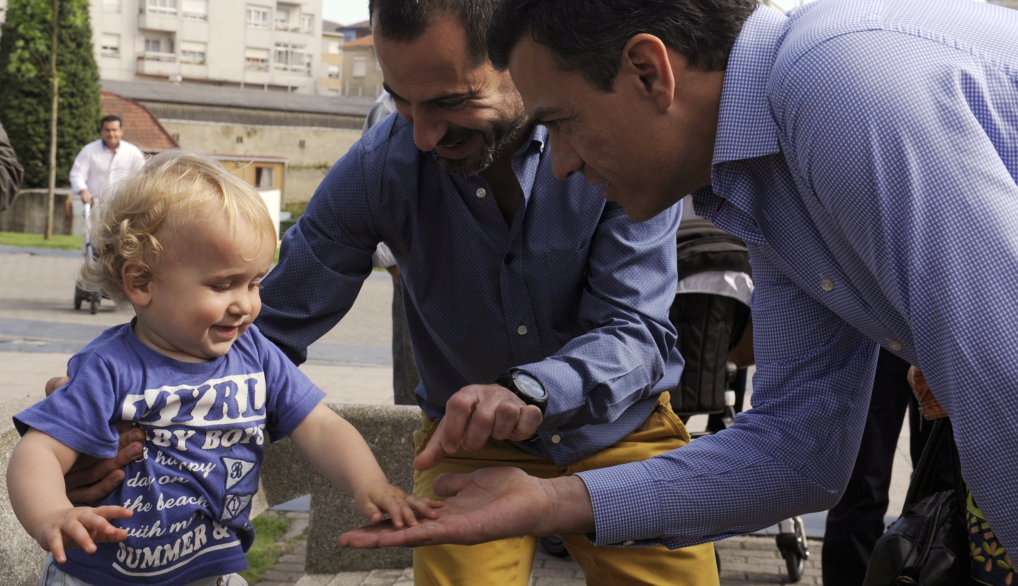 Spain's opposition Socialist Party leader Pedro Sanchez and Angel Garcia, candidate for mayor of Pola de Siero, greet a child during a walk around the village of Lugones, northern Spain