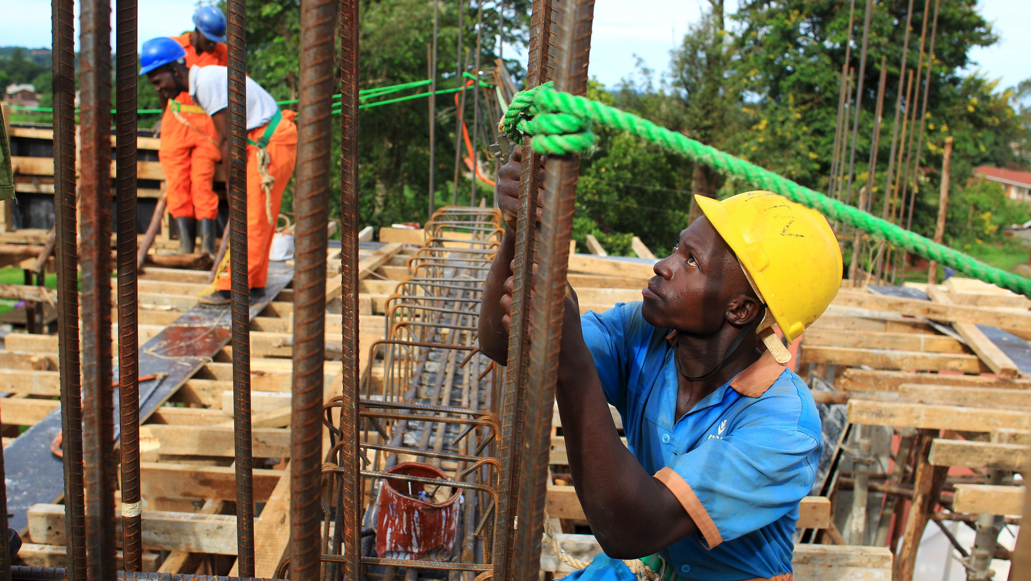 A construction worker fastens metal bars on the rooftop of a new hospital under construction in Hoima