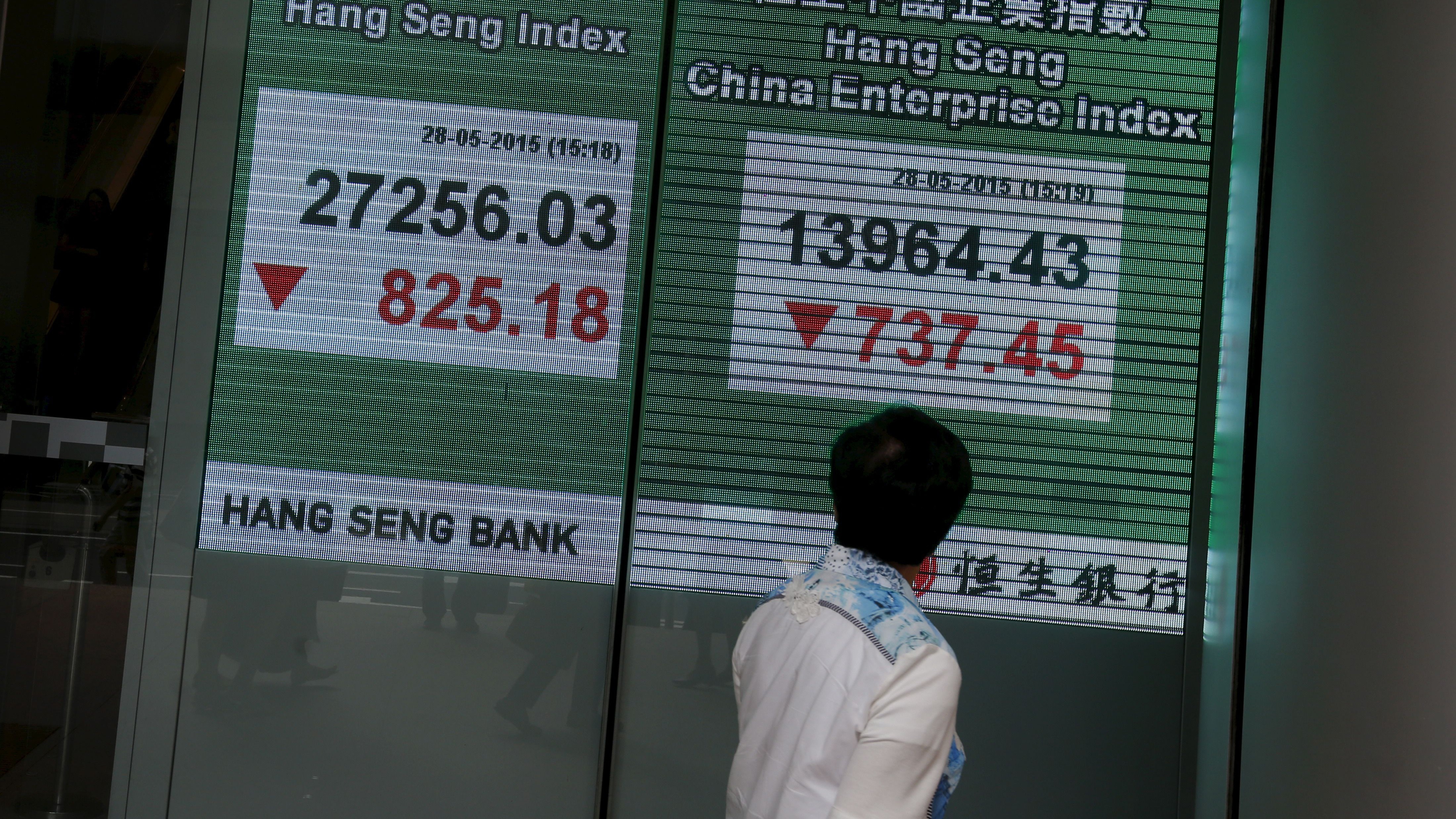 A passerby looks at a panel displaying the blue-chip Hang Seng Index outside a bank in Hong Kong
