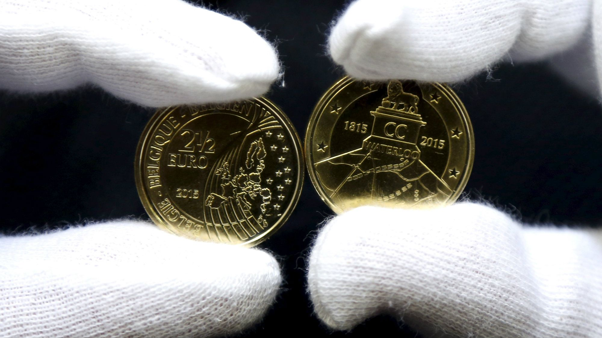 A worker displays newly minted commemorative 2.5 euro coins to mark the bicentennial of the battle of Waterloo, at Belgium's Royal Mint in Brussels June 8, 2015.