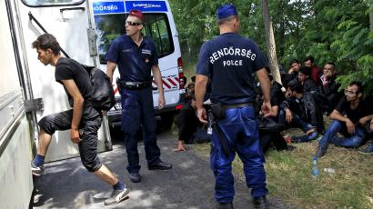 Migrants are detained by Hungarian police after crossing the Hungarian-Serbian border illegally.