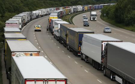 A police vehicle drives past lorries are backed up on the M20 motorway which leads from London to the Channel Tunnel terminal at Ashford and the Ferry Terminal at Dover, June 23, 2015.