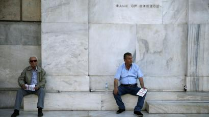 Pensioners rest in front of the Bank of Greece building before an anti-austerity demonstration in Athens, Greece June 23, 2015.