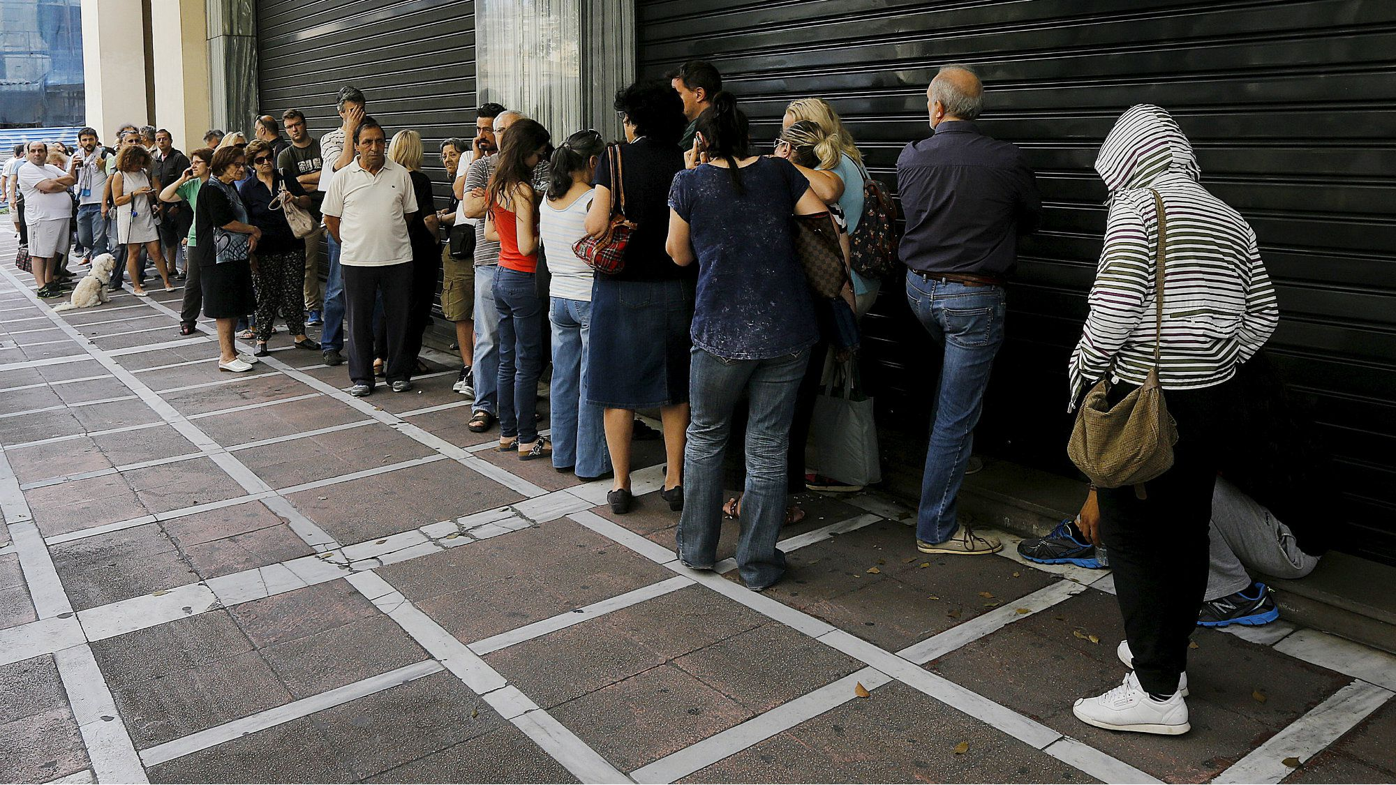 People wait outside a closed branch of Piraeus Bank in Athens, Greece June 27, 2015.