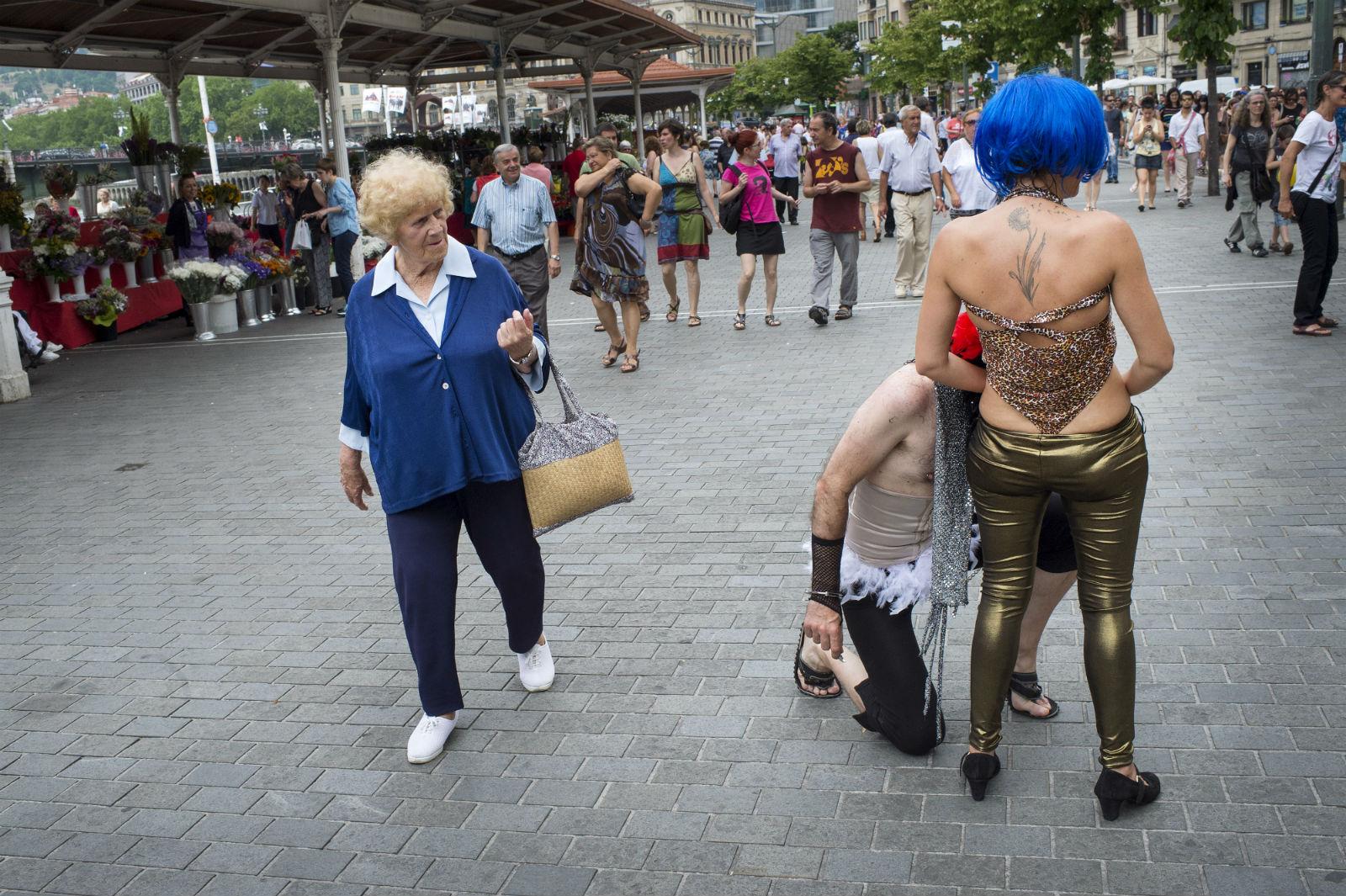 A woman walks past participants at a gay pride in Bilbao