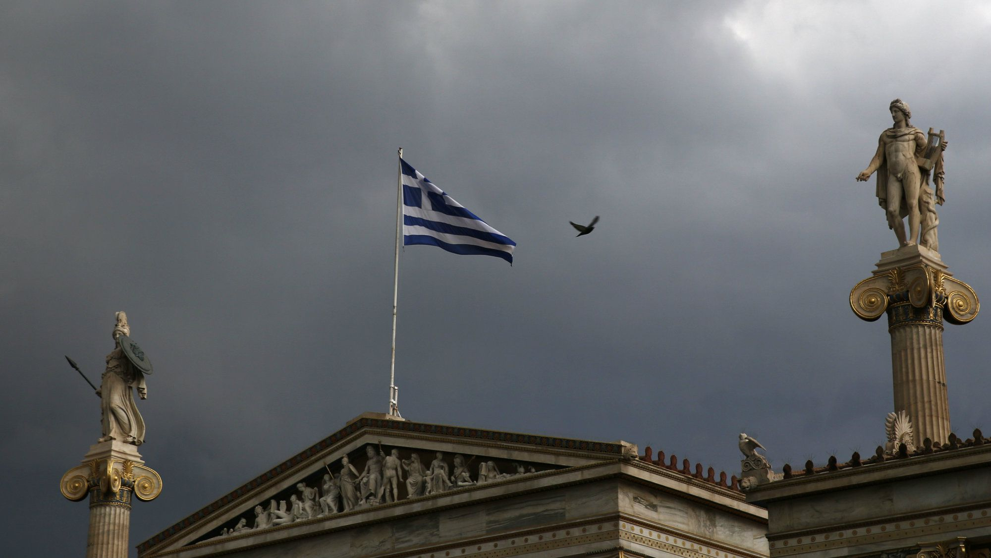 A Greek national flag flutters atop the university building as dark clouds fill the sky in Athens, Greece, June 30, 2015.