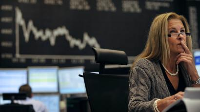 A share trader checks share prices as she sits behind her trading terminals at the trading floor of the German stock exchange in Frankfurt.