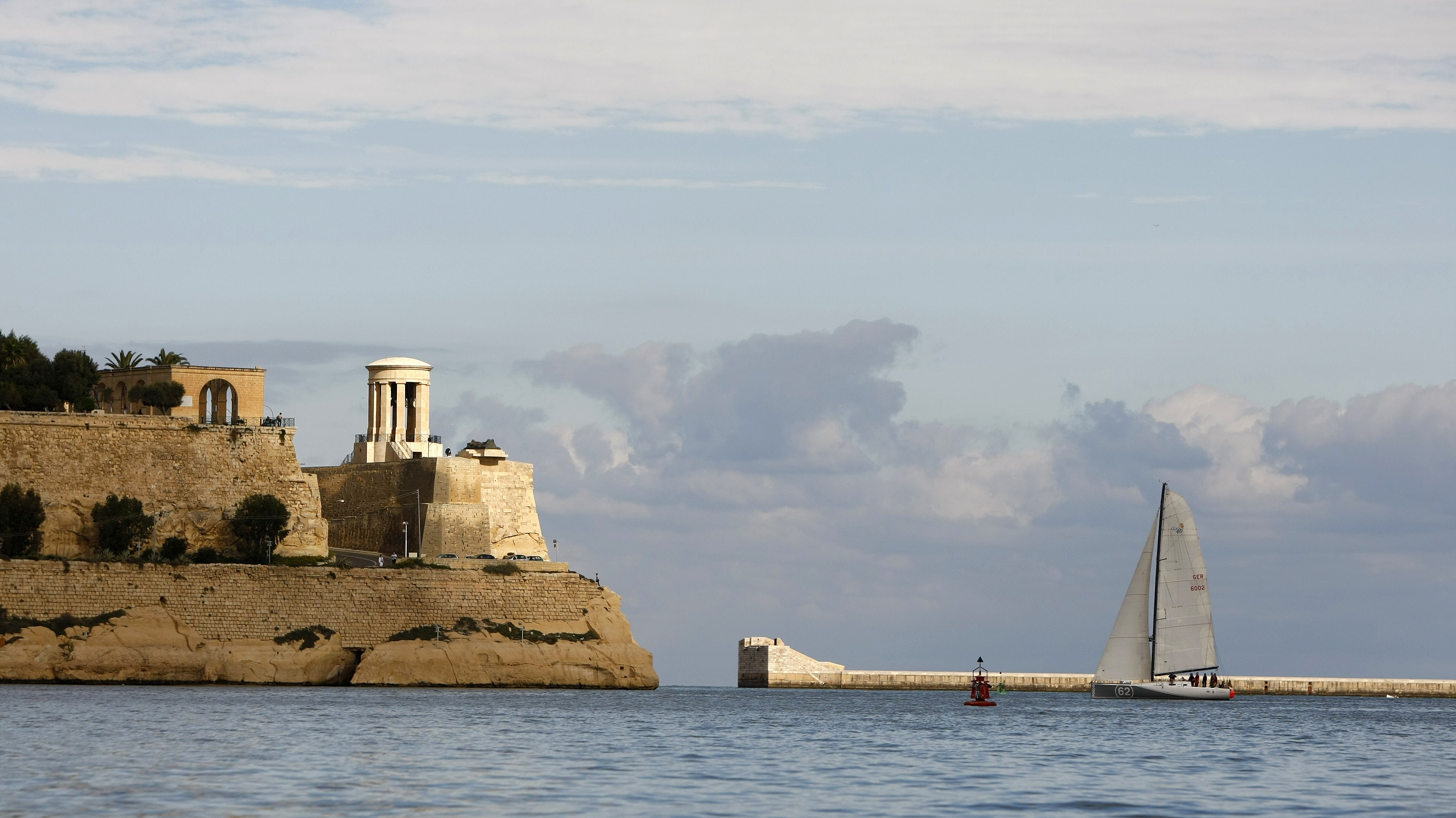 A yacht sails into Valletta's Grand Harbour.