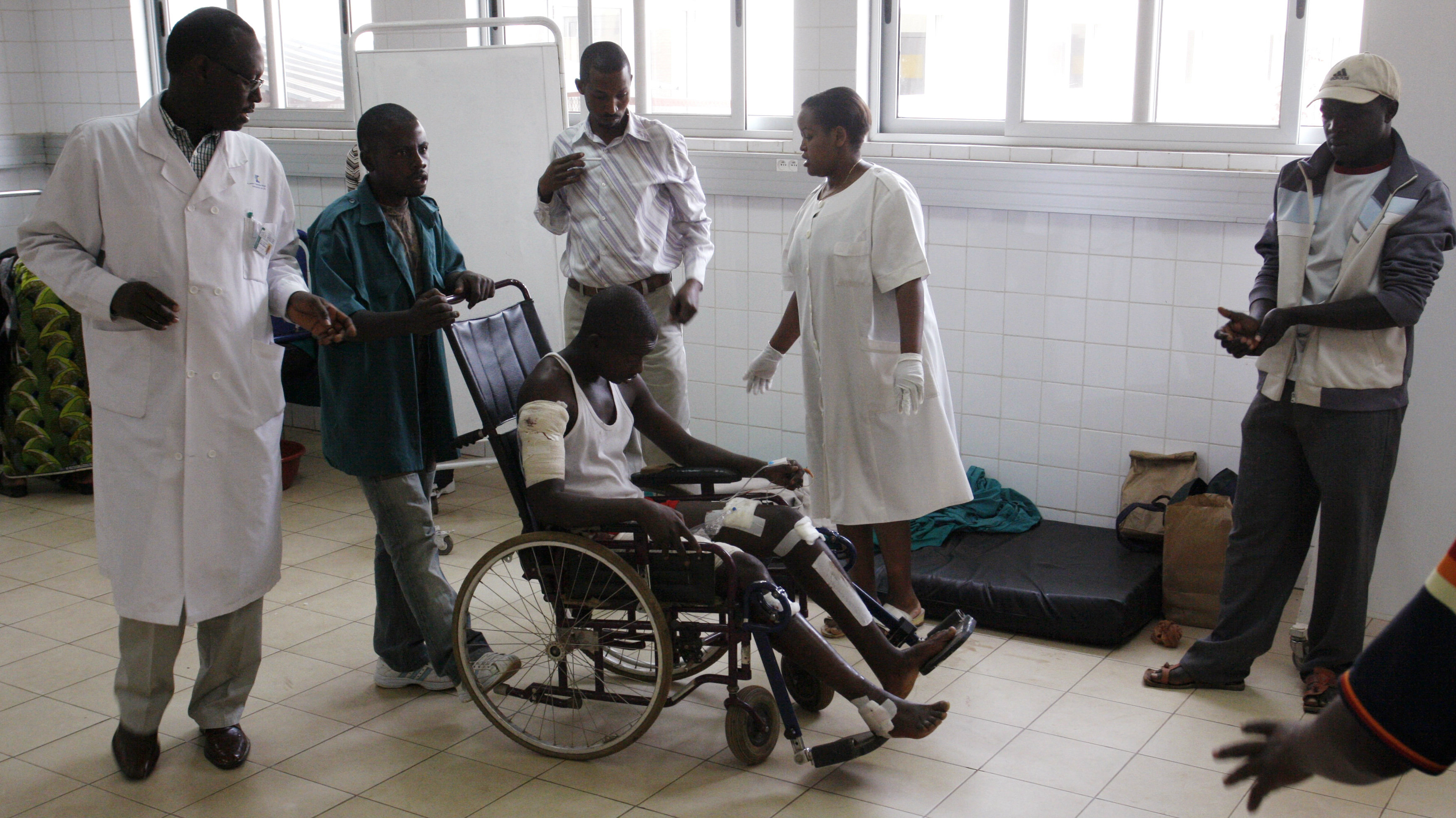 A grenade attack victim (in a wheelchair) is assisted inside a ward at the university hospital in Rwanda's capital Kigali August 12, 2010. Incumbent Paul Kagame won 93 percent of the votes in Rwanda's presidential election, final results showed on Wednesday, after a campaign that critics said was marred by government repression. A grenade was thrown into a rush-hour crowd in the capital Kigali, wounding at least seven people. Analysts said the attack appeared to be aimed at producing a political crisis. REUTERS/Hereward Holland
