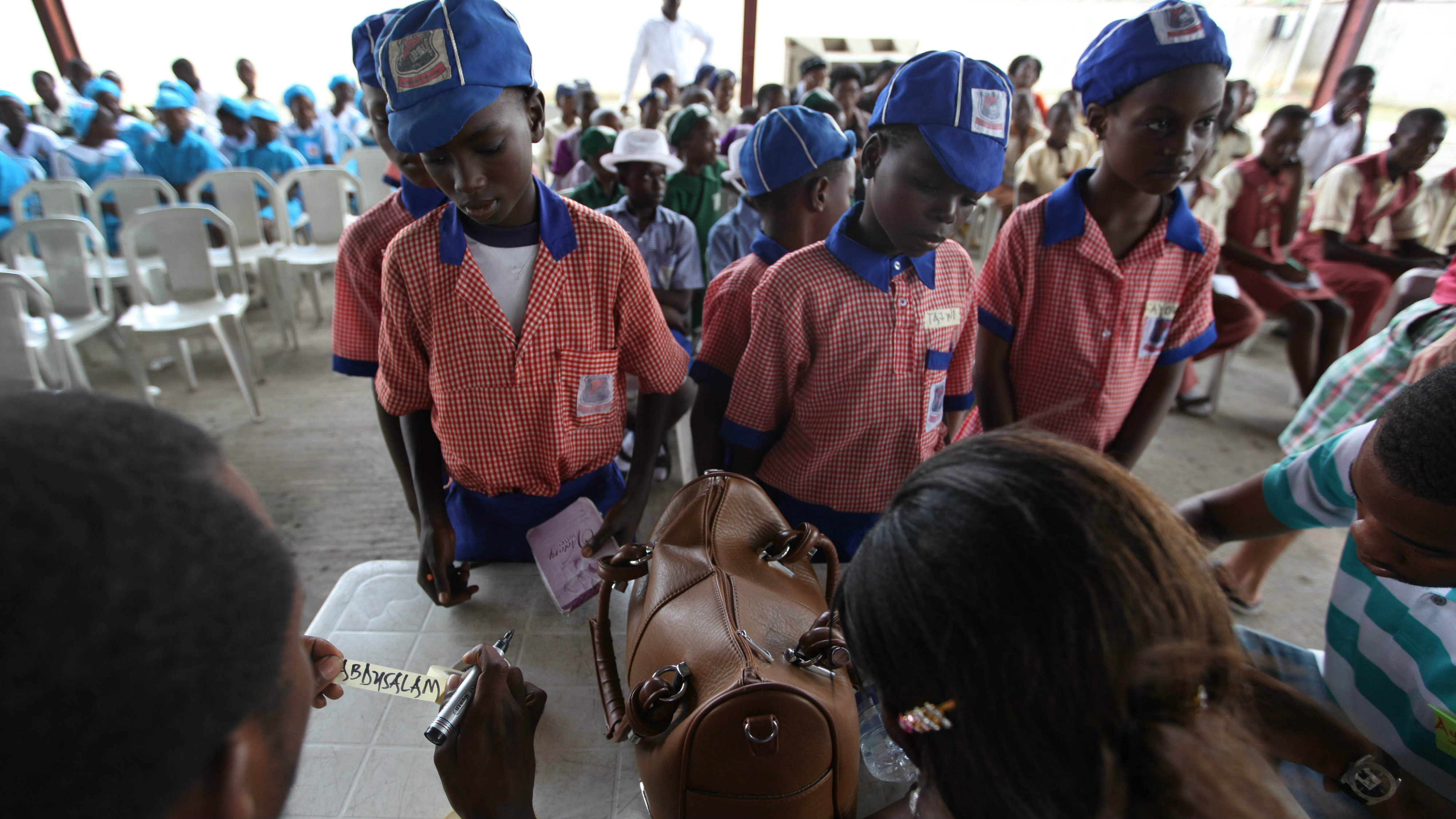 Children wait for name tags at a science fair in Lagos, Nigeria, on Tuesday, Nov. 6, 2012. Young children with inventions flocked to the Maker Faire Africa in Lagos this week to show off their creations. While Nigeria faces challenges from a lack of state-run power and poor schooling, organizers hope the fair will inspire children to pursue their interest in science and technology. (AP Photo/Jon Gambrell)