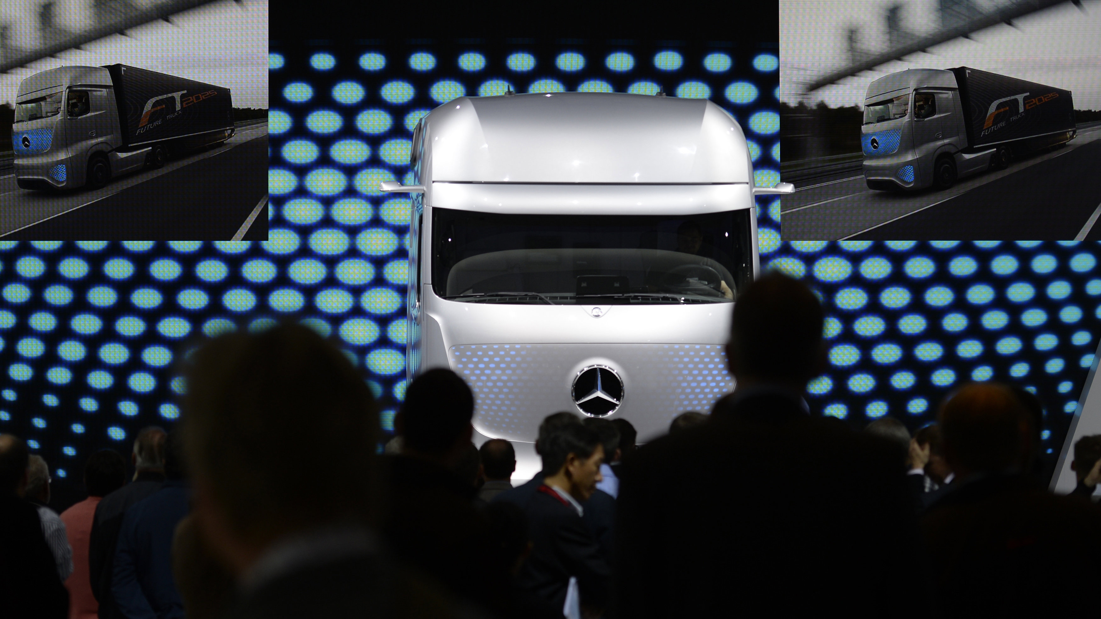 Visitors look at a concept driverless truck at the booth of German truck maker Mercedes Benz at the IAA truck show in Hanover, September 26, 2014. The IAA 2014 will run until October 2, 2014.