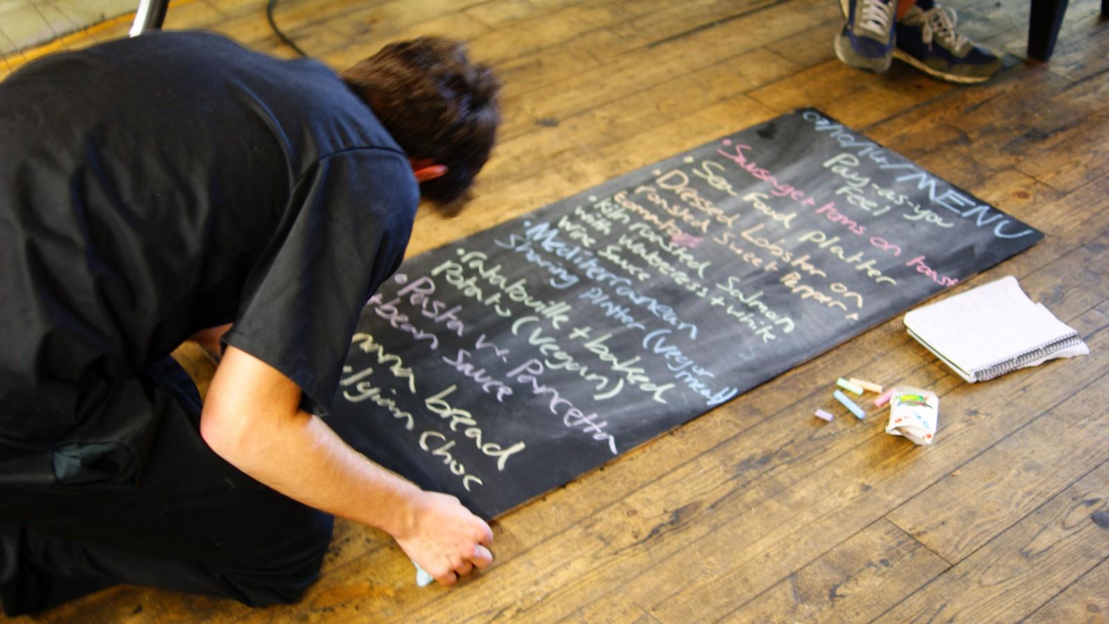 A volunteer writes a menu at Bristol Skipchen.