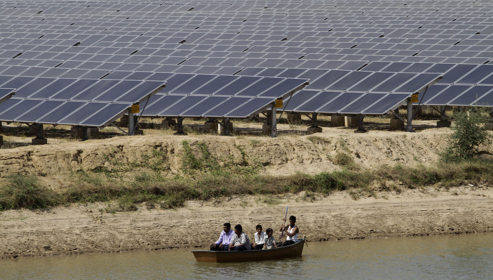 Locals on a boat pass by panels at a newly inaugurated solar energy farm at Gunthawada in Gujarat state, about 175 kilometers (109 miles) north of Ahmadabad, India, Friday, Oct. 14, 2011. The 30 mega-watt solar farm built by Moser has been set up with an investment of Rupees 4.65 billion (US $96,875,000) and uses 236,000 thin film modules, according to an official release.