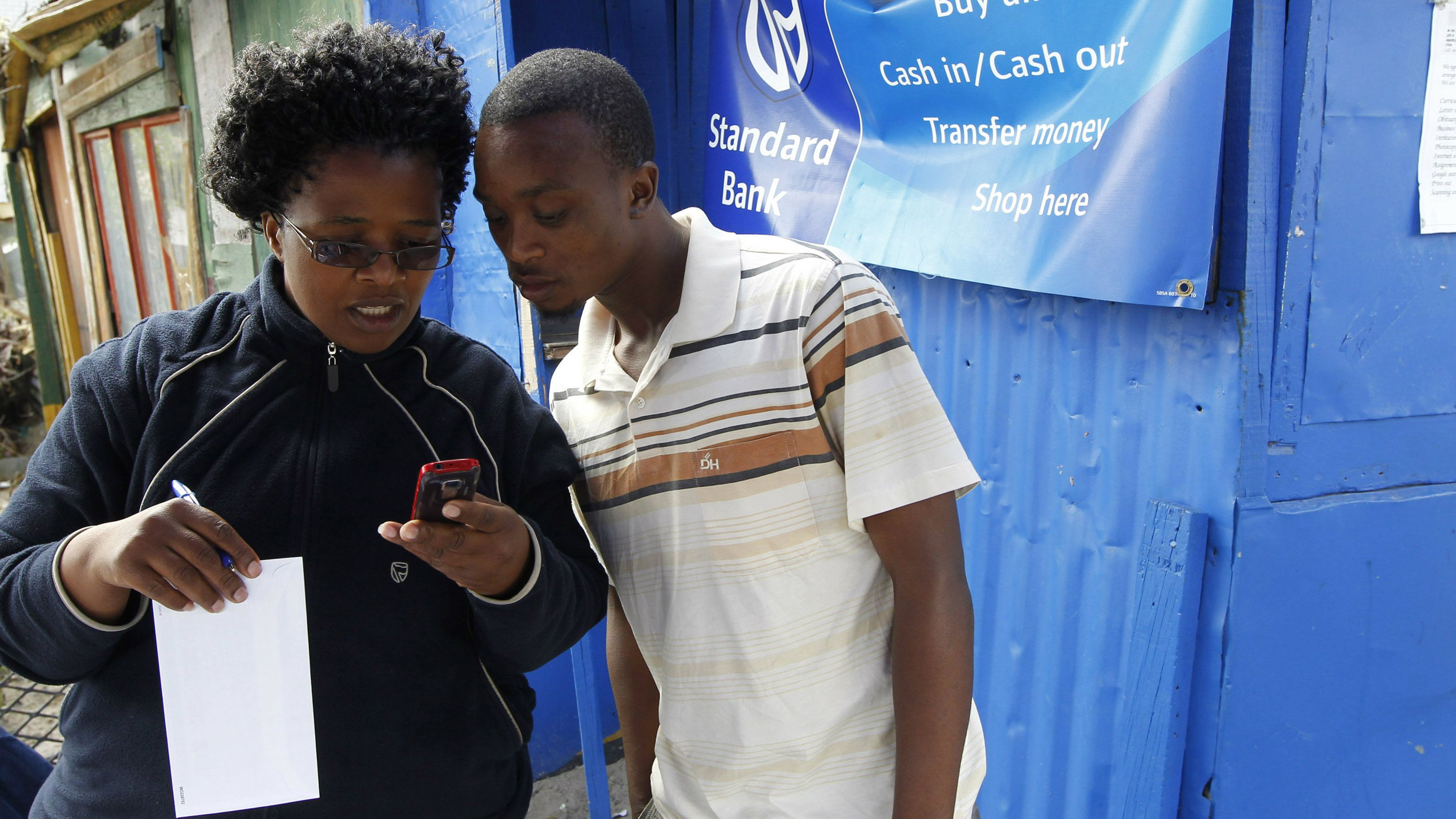 Staff from South Africa's Standard Bank show a newly signed client how to use mobile phone banking as part of a drive to take banking to poorer areas in Cape Town's Khayelitsha township, June 28, 2011. REUTERS/Mike Hutchings (SOUTH AFRICA