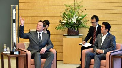 SpaceX and Tesla Motors Inc. CEO Elon Musk, left, talks with Japanese Prime Minister Shinzo Abe, right, while showing a miniature model of a SpaceX rocket during a courtesy call at the latter's official residence in Tokyo Tuesday, Sept. 9, 2014.