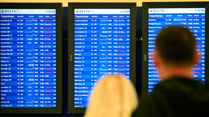 In this Feb. 25, 2015 file photo, airline passengers look at departure screens with flight cancellations posted as a winter storm bringing a mix of snow, sleet and rain resulted in an FAA-ordered ground stop at Hartsfield-Jackson International Airport in Atlanta.