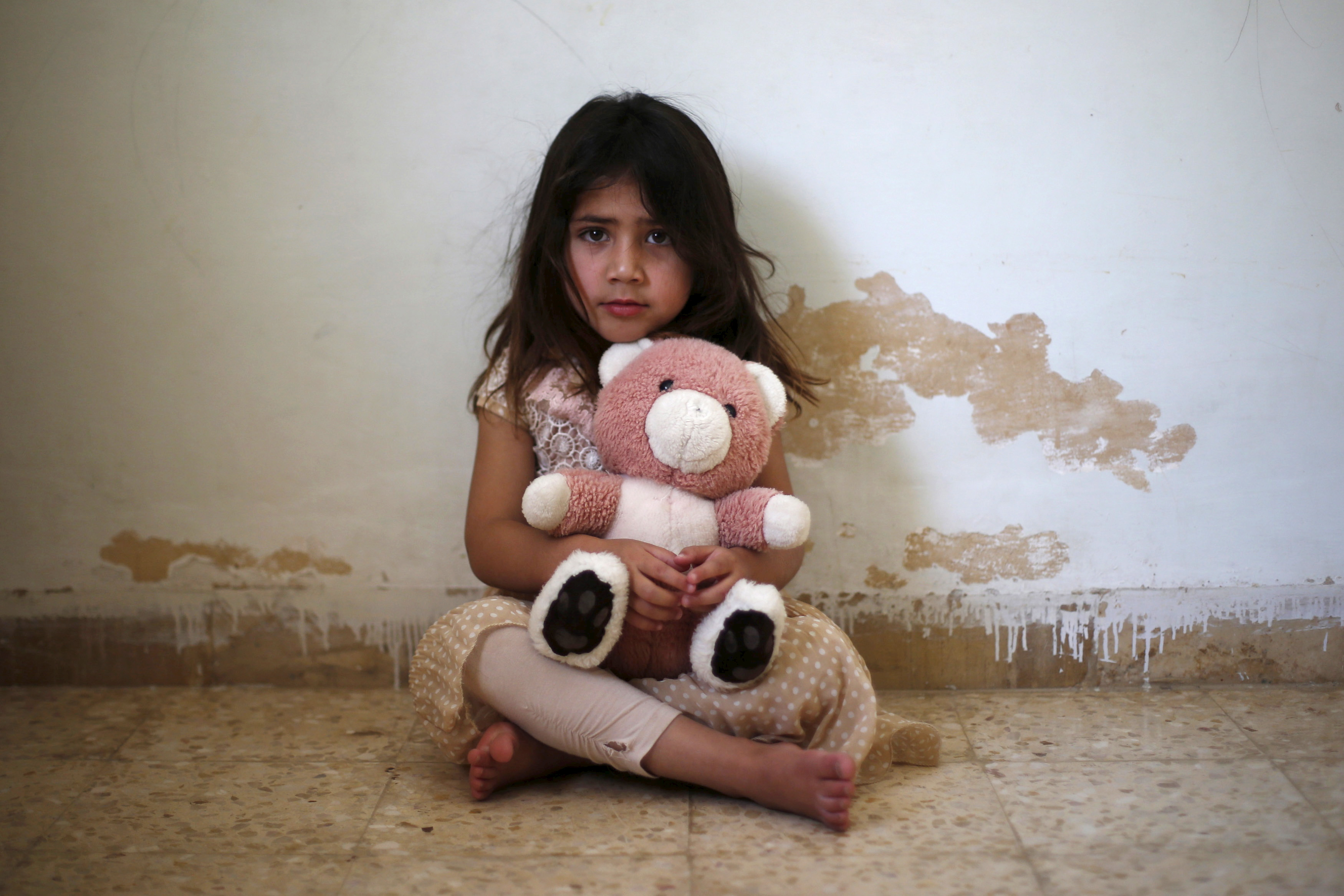 Asmaa, the daughter of Abdul Rahaman al-Sarhan, a blind Syrian refugee, poses with her toy as she plays in her family home in the city of Zarqa, Jordan, June 18, 2015. Sarhan and his family of seven fled from their home in Damascus to Jordan about two and a half years ago. After the World Food Program reduced their humanitarian aid vouchers, Sarhan's sons, Jaber, 15, and Mohammad, 13, had to leave school in Zarqa in Jordan, to find jobs to help feed the family.