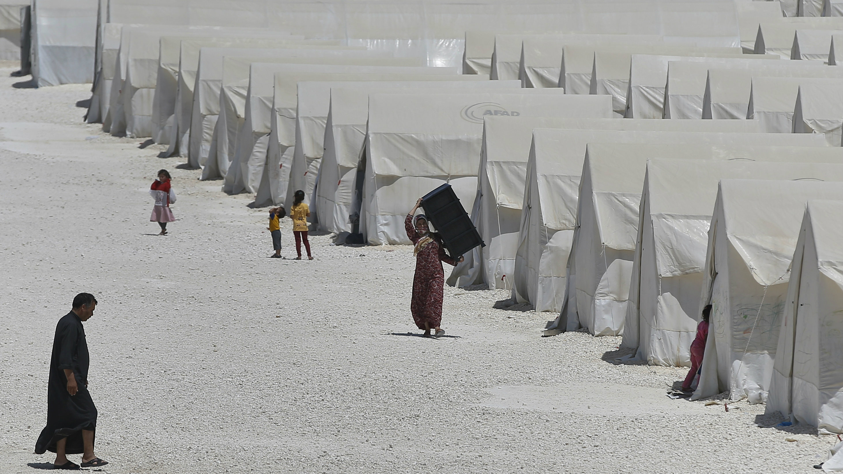 Syrian refugees walk around a refugee camp in Suruc, on the Turkey-Syria border, Friday, June 19, 2015. Ahead of World Refugee Day on Saturday, June 20, 2015, the UN refugee agency, UNHCR, estimated that a total of 11.6 million people from Syria had been displaced by the conflict by the end of last year, the largest such figure worldwide. Turkey is the world's biggest refugee host with 1.59 million refugees, according to the most recent U.N. figures.