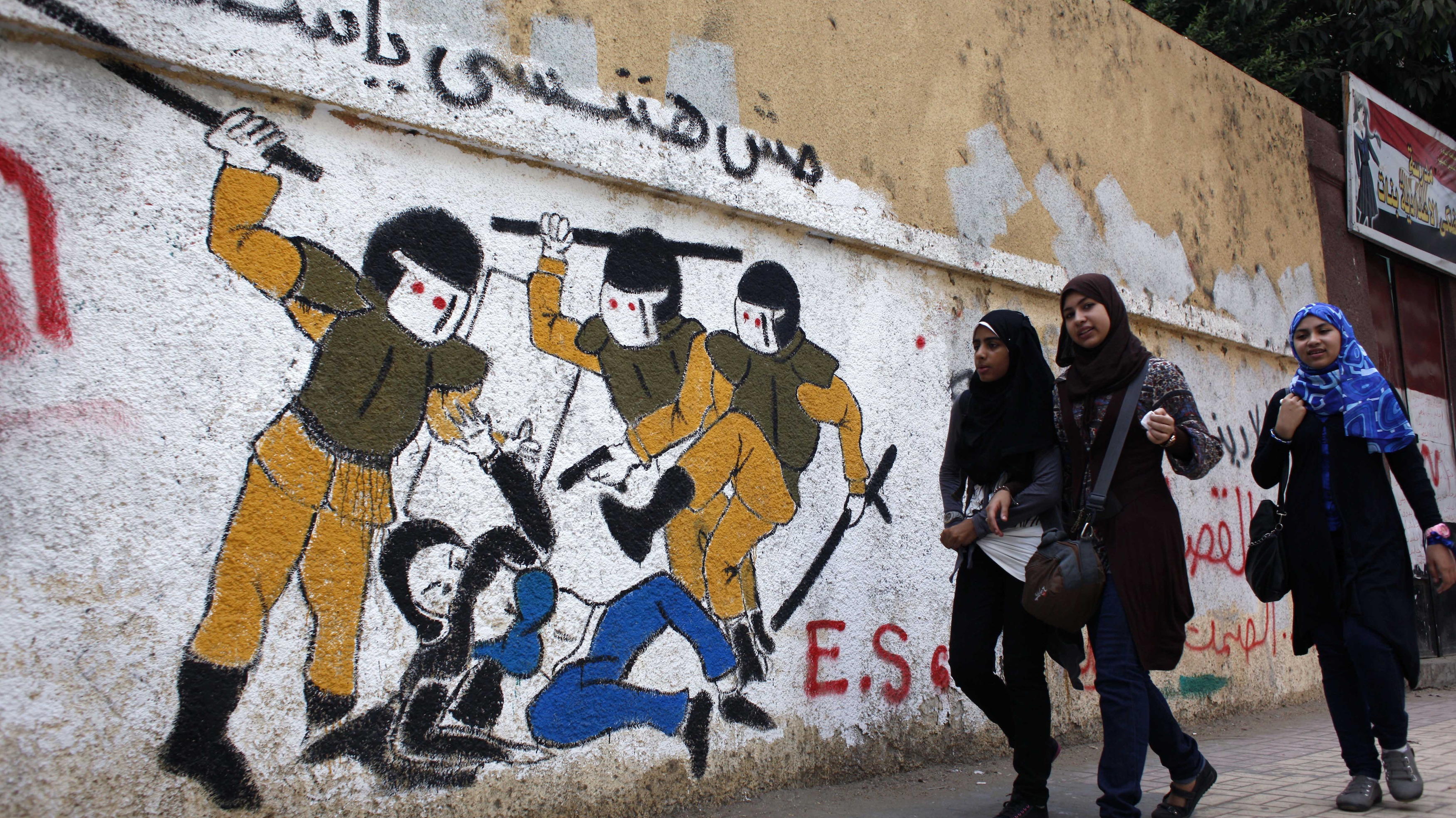 Egyptian girls walk past a mural in Tahrir Square, Cairo.