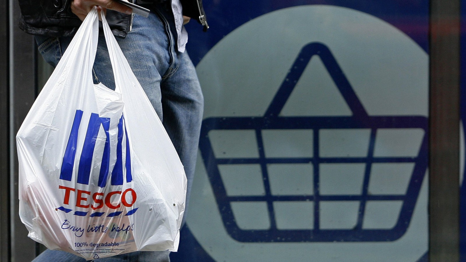 A man carries a carrier bag as he leaves a Tesco supermarket.