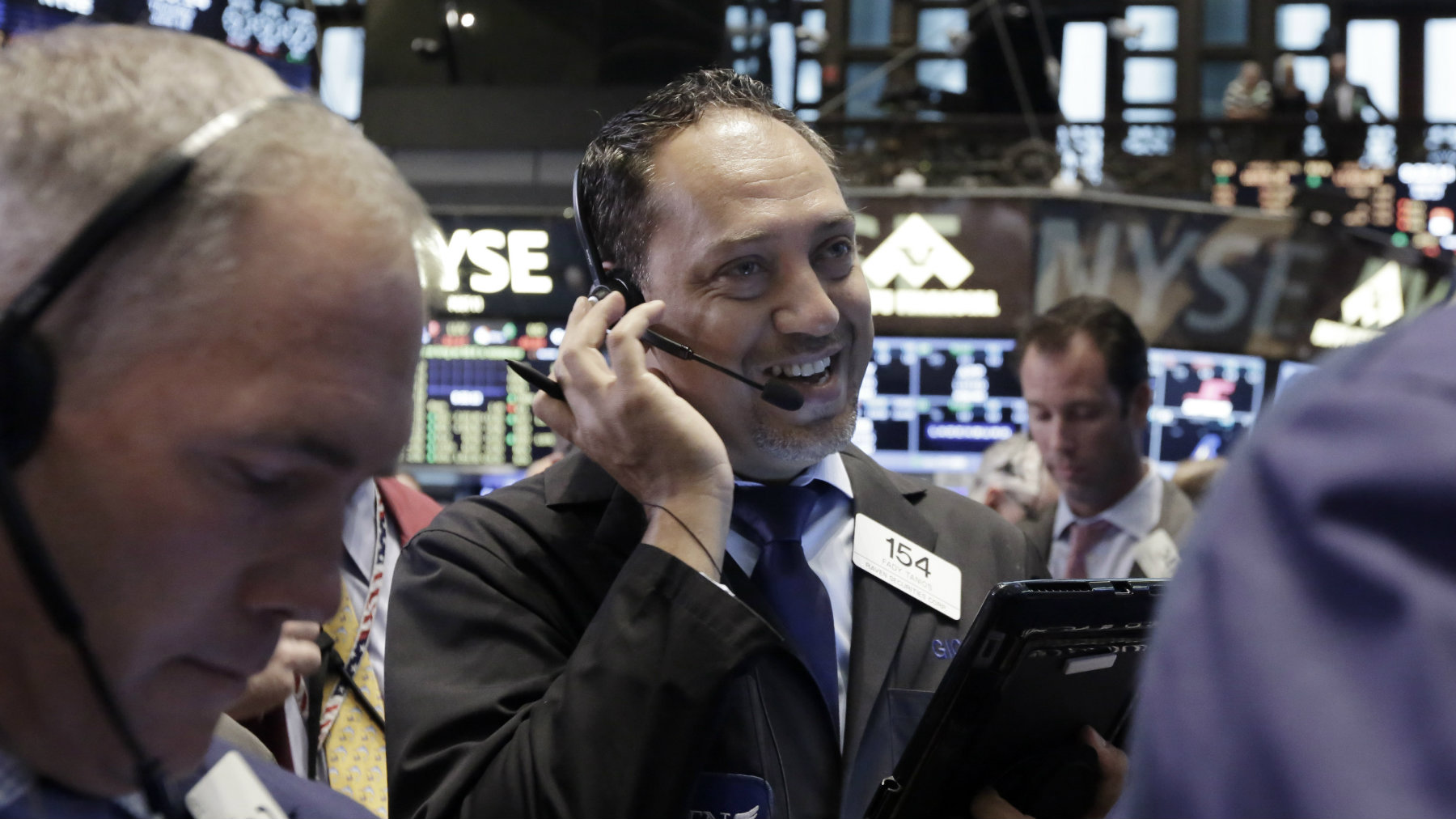 Trader Fady Tanios, center, works on the floor of the New York Stock Exchange, Thursday, June 18, 2015. U.S. stocks moved higher in early trading Thursday, extending gains a day after the Federal Reserve left interest rates unchanged from historically low levels. Health care stocks were among the biggest gainers. (AP Photo/Richard Drew)