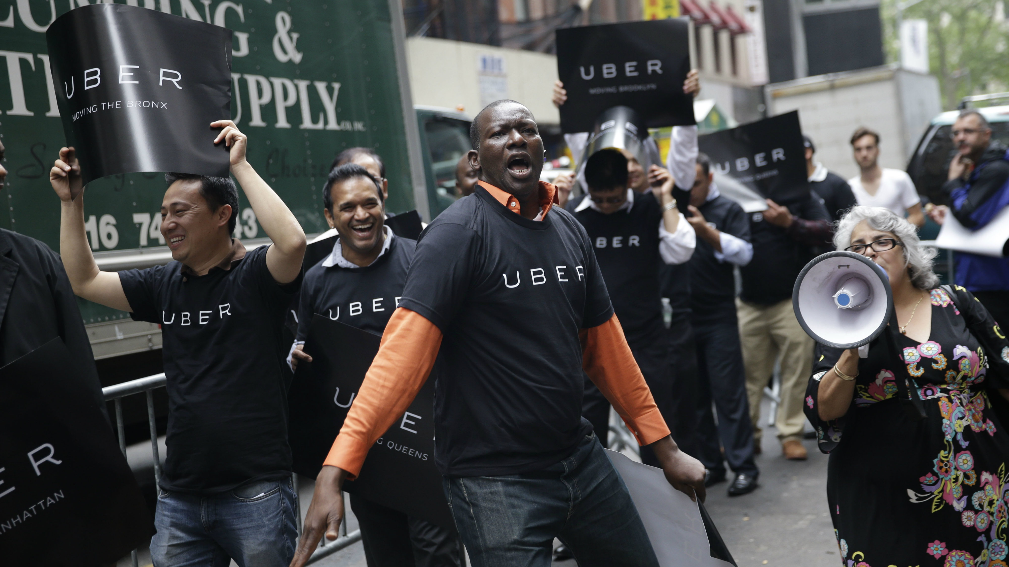 Uber drivers and their supporters protest in front of the offices of the Taxi and Limousine Commission in New York, Thursday, May 28, 2015. Uber and Lyft are pushing back against a New York City effort to regulate app-based car services. The proposal before the Taxi and Limousine Commission would require car services that riders can summon with their phones to comply with many of the rules that govern the yellow cabs they compete with. (AP Photo/Seth Wenig)