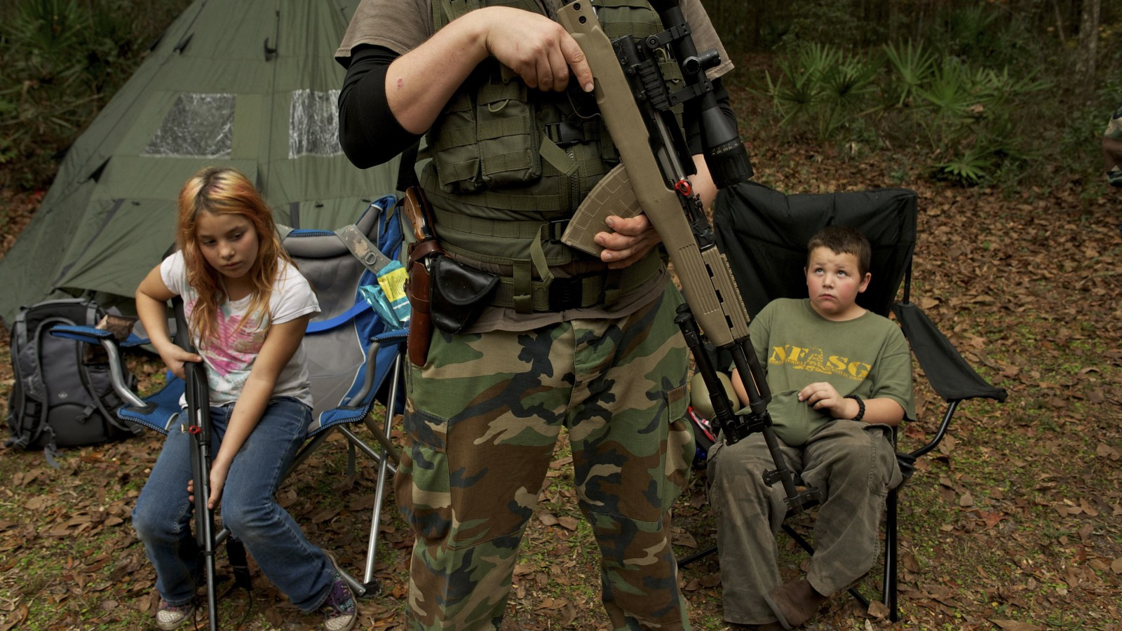 """Members of the North Florida Survival Group wait with their rifles before heading out to perform enemy contact drills during a field training exercise in Old Town, Florida, December 8, 2012. The group trains children and adults alike to handle weapons and survive in the wild. The group passionately supports the right of U.S. citizens to bear arms and its website states that it aims to teach """"patriots to survive in order to protect and defend our Constitution against all enemy threats"""". Picture taken December 8, 2012.   REUTERS/Brian Blanco  (UNITED STATES - Tags: SOCIETY POLITICS TPX IMAGES OF THE DAY)  ATTENTION EDITORS: PICTURE 19 OF 20 FOR PACKAGE 'TRAINING CHILD SURVIVALISTS' SEARCH 'FLORIDA SURVIVAL' FOR ALL IMAGES - RTR3E4D6"""