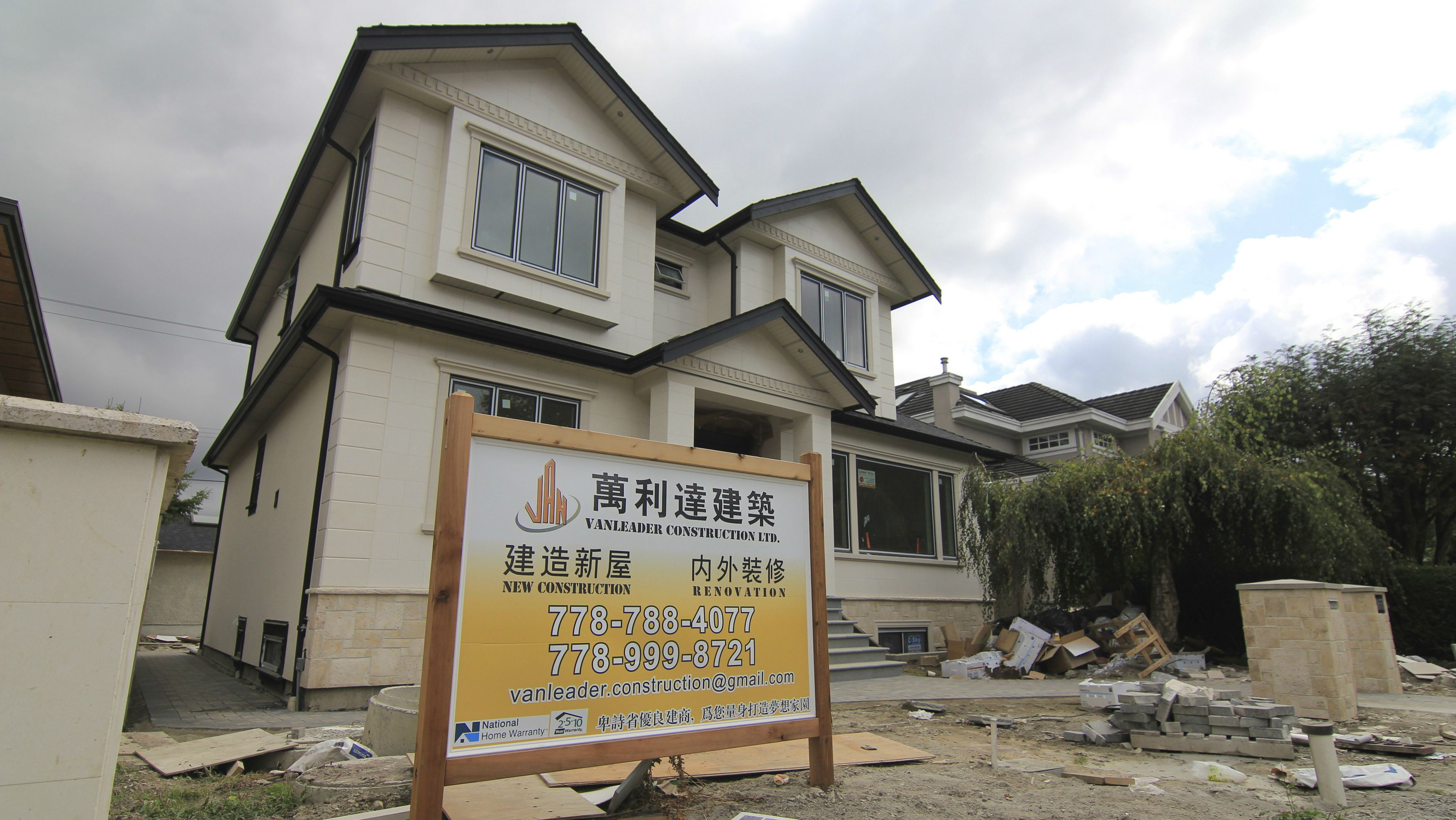 A contractor's sign stands outside a mansion currently under construction in a Vancouver neighbourhood popular with Chinese buyers September 9, 2014. Chinese investors' global hunt for prime real estate is helping drive Vancouver home prices to record highs and the city, long among top destinations for wealthy mainland buyers, is feeling the bonanza's unwelcome side-effects. The latest wave of Chinese money is flowing into luxury hot spots. But it has also started driving up housing costs elsewhere in a city which already ranks as North America's least affordable urban market. Picture taken September 9. REUTERS/Julie Gordon (CANADA - Tags: REAL ESTATE BUSINESS)