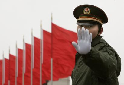 A soldier gestures to the photographer as he stands guard at the Tiananmen Square in Beijing March 4, 2007. China's will boost defence spending by 17.8 percent in 2007, accelerating the emerging power's string of annual double-digit rises in money for a modern military that reflects its economic strength. REUTERS/Joe Cha