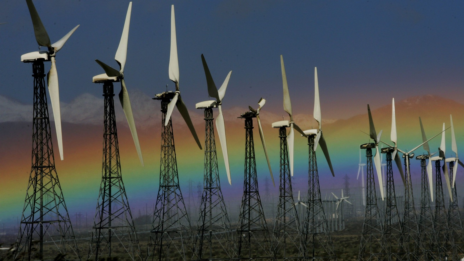 This Jan. 28, 2008 file photo shows a rainbow visible looking West from Palm Springs, Calif. next to an array of wind turbines. Interior Secretary Sally Jewell on Tuesday, Sept. 23, 2014, unveiled a proposed roadmap for developing massive solar and wind projects in California's Mojave Desert.
