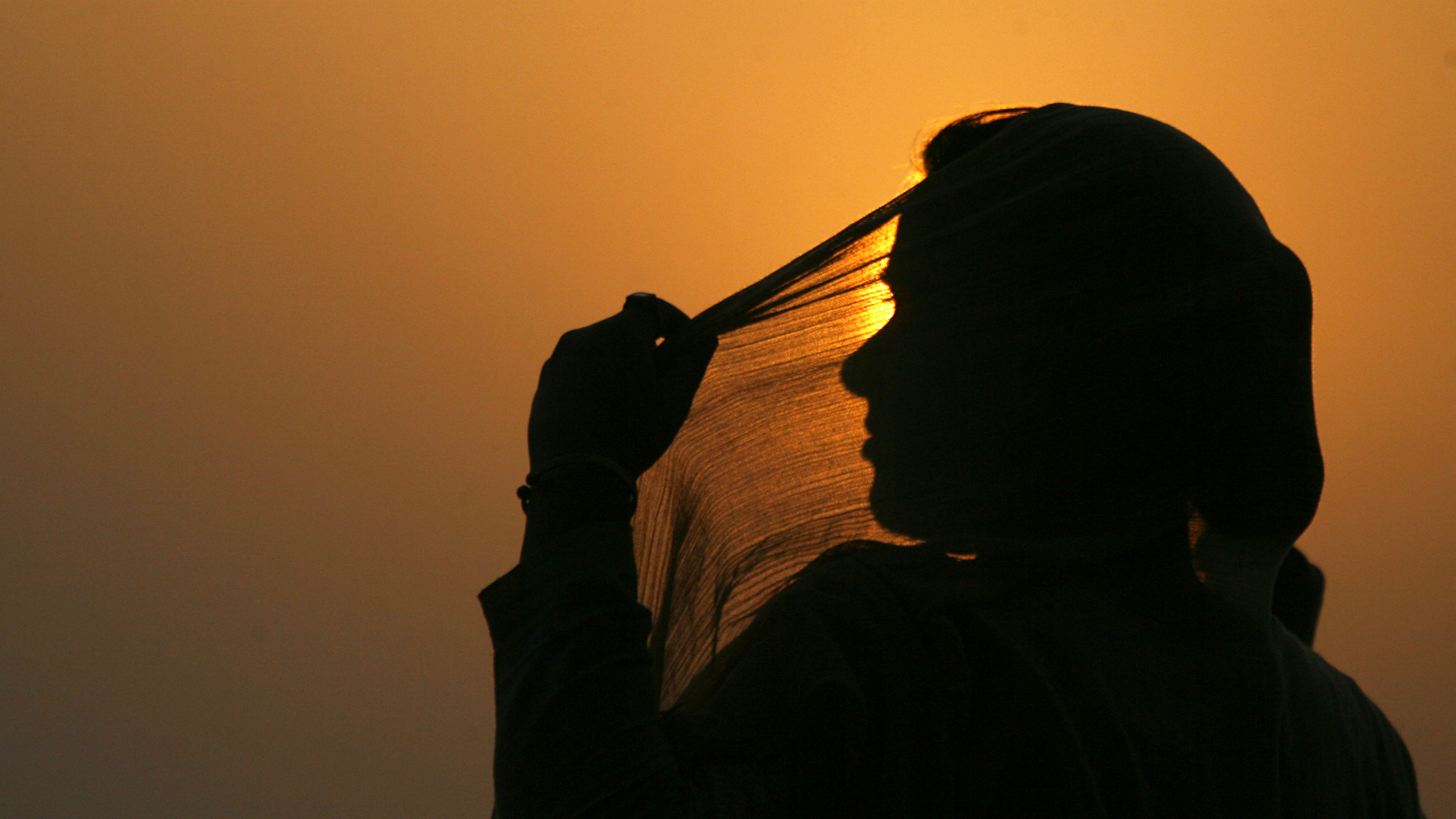 A woman adjusts her scarf as the sun sets over Kashmir's Dal Lake in Srinagar July 18, 2010. REUTERS/Danish Ismail (INDIAN-ADMINISTERED KASHMIR - Tags: ENVIRONMENT SOCIETY)