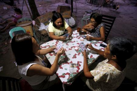 Women play a Russian poker card game in Angeles city, north of Manila.