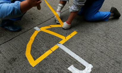 Workers remove a symbol of Hong Kong's pro-democracy movement from a street.