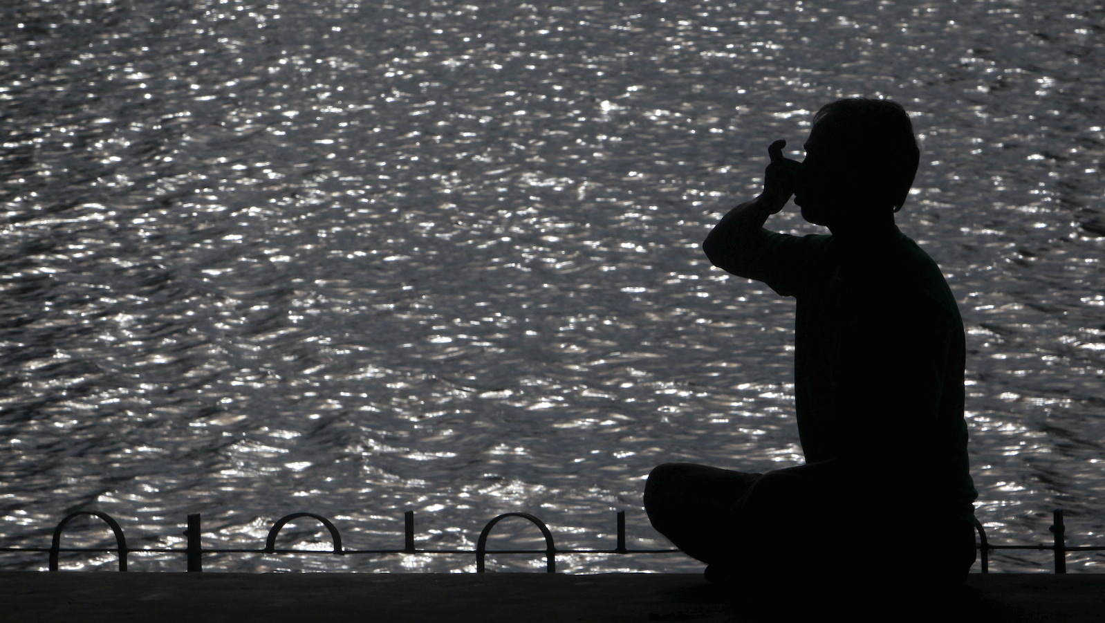 A man practices yoga on the promenade next to a lake in Agartala, India early June 16, 2015.